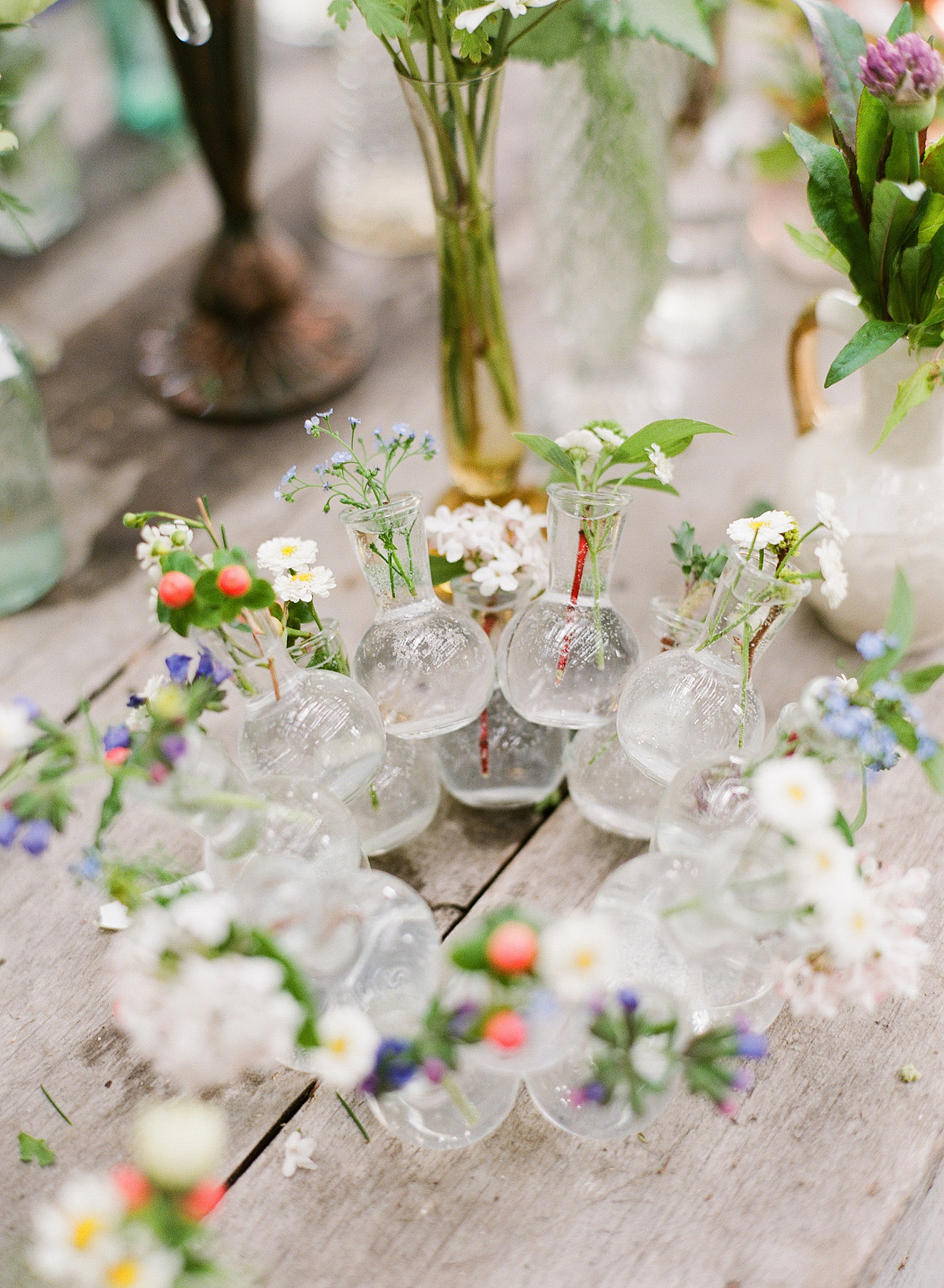 a wreath of vases with springtime buds sits on a farm table while destination wedding photographer Lexia Frank photographs this springtime wedding on film at the Northwind Perennial Gardens in wisconsin