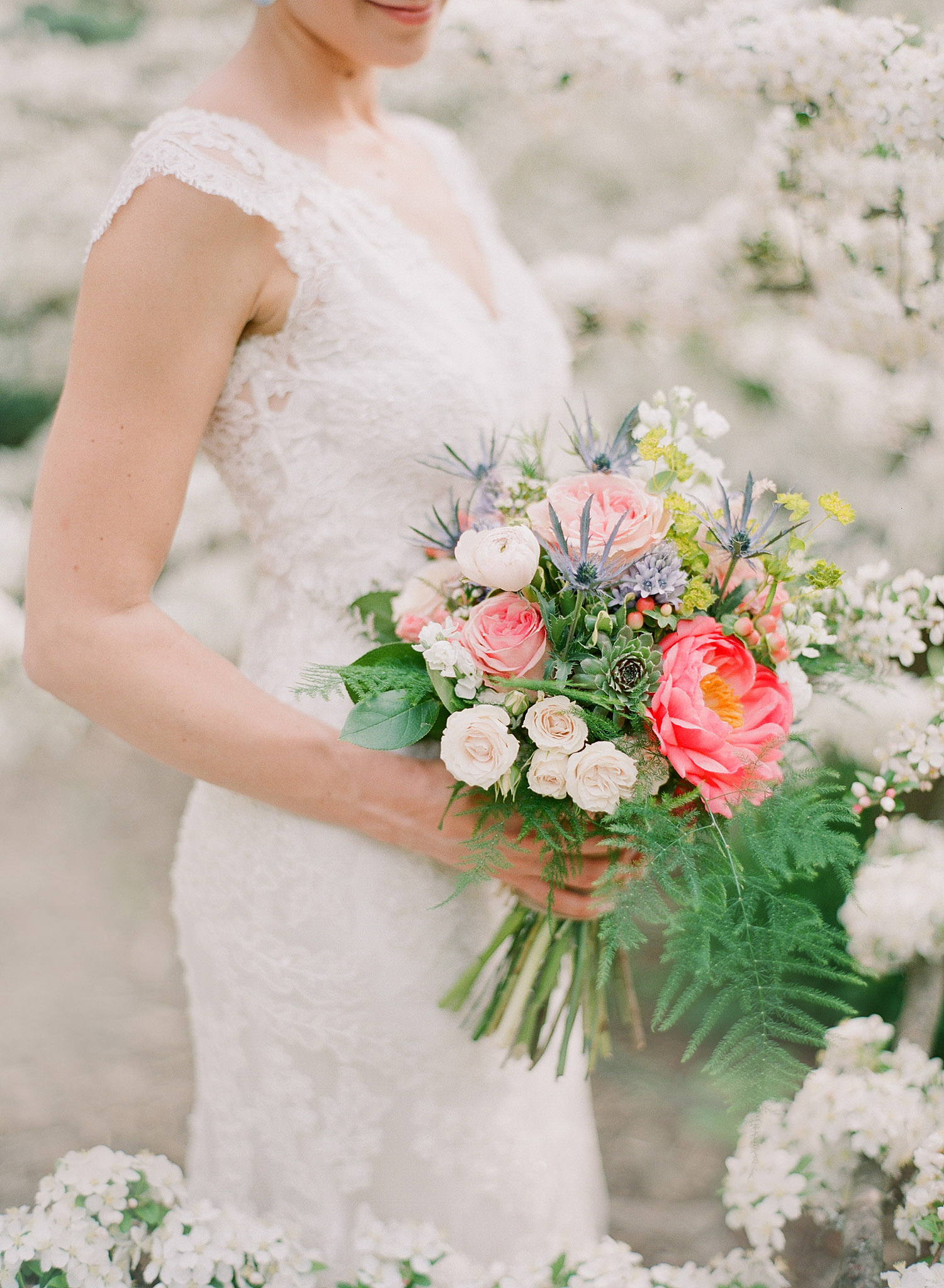 Bride holds asymetrical bouquet of terms and ranunculus succulents and roses as she stands in the springtime blooms of Northwind Perennial Gardens in wisconsin while Lexia Frank, destination wedding photographer, photographs on film
