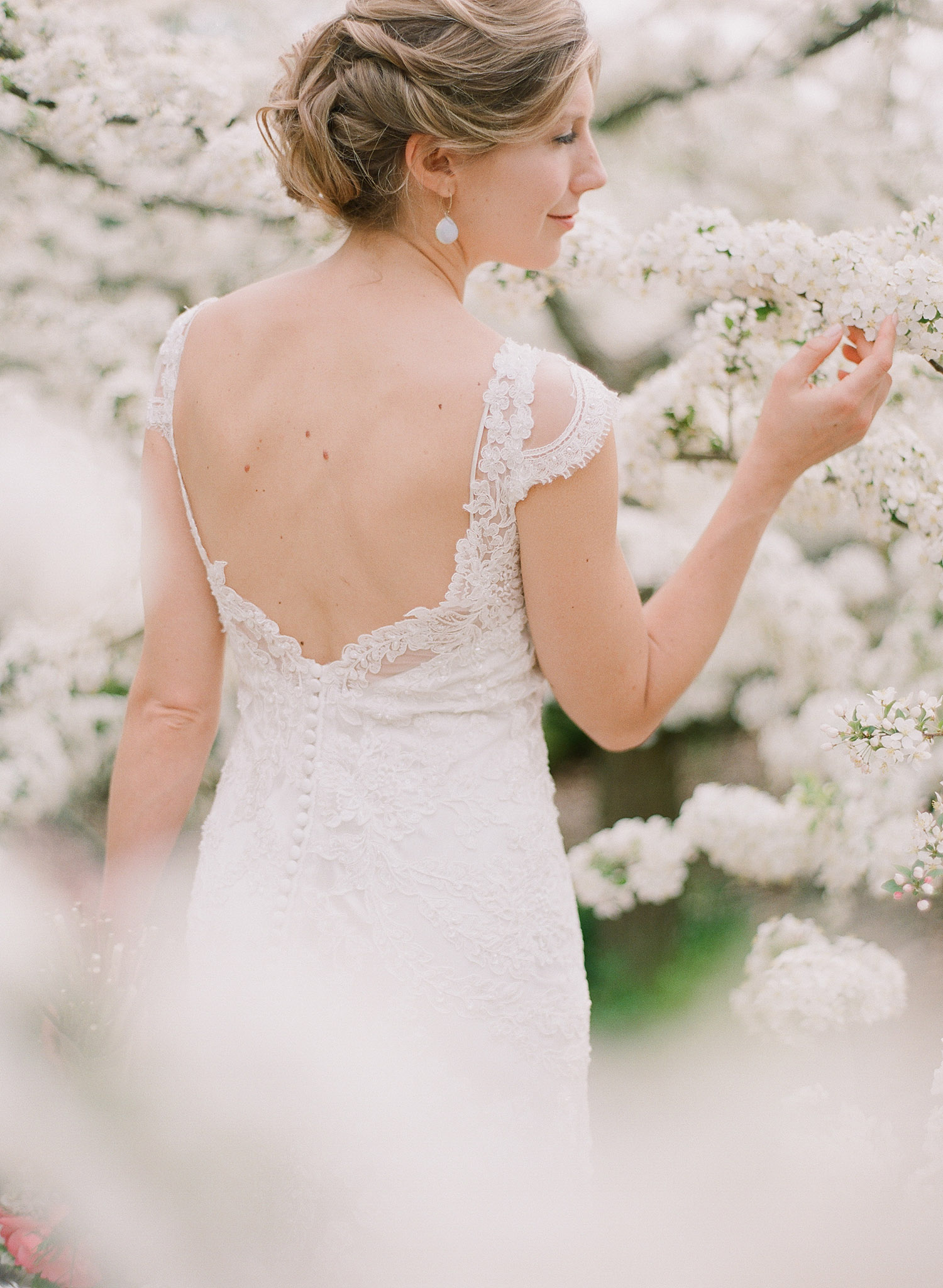bride wears lace wedding dress with cap sleeves and smells the springtime blooms at her springtime wedding at Northwind Perennial Gardens in wisconsin while Destination wedding photographer Lexia Frank photographs her wedding on film