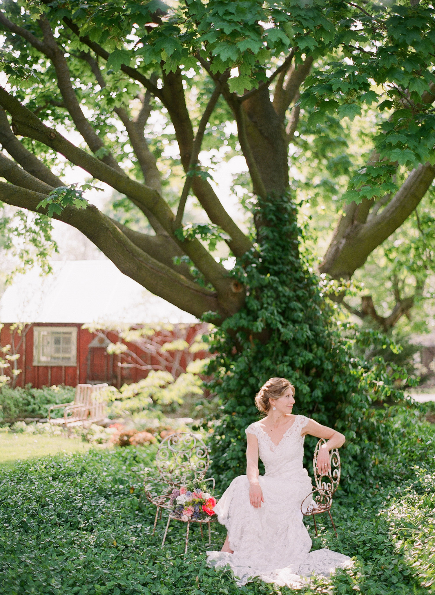 bride sits on a vintage wrought iron chair in ivy under a tree at this springtime wedding at Northwind Perennial Garden - a beautiful wisconsin wedding venue - while Destination wedding photographer Lexia Frank Photographs this wedding on film