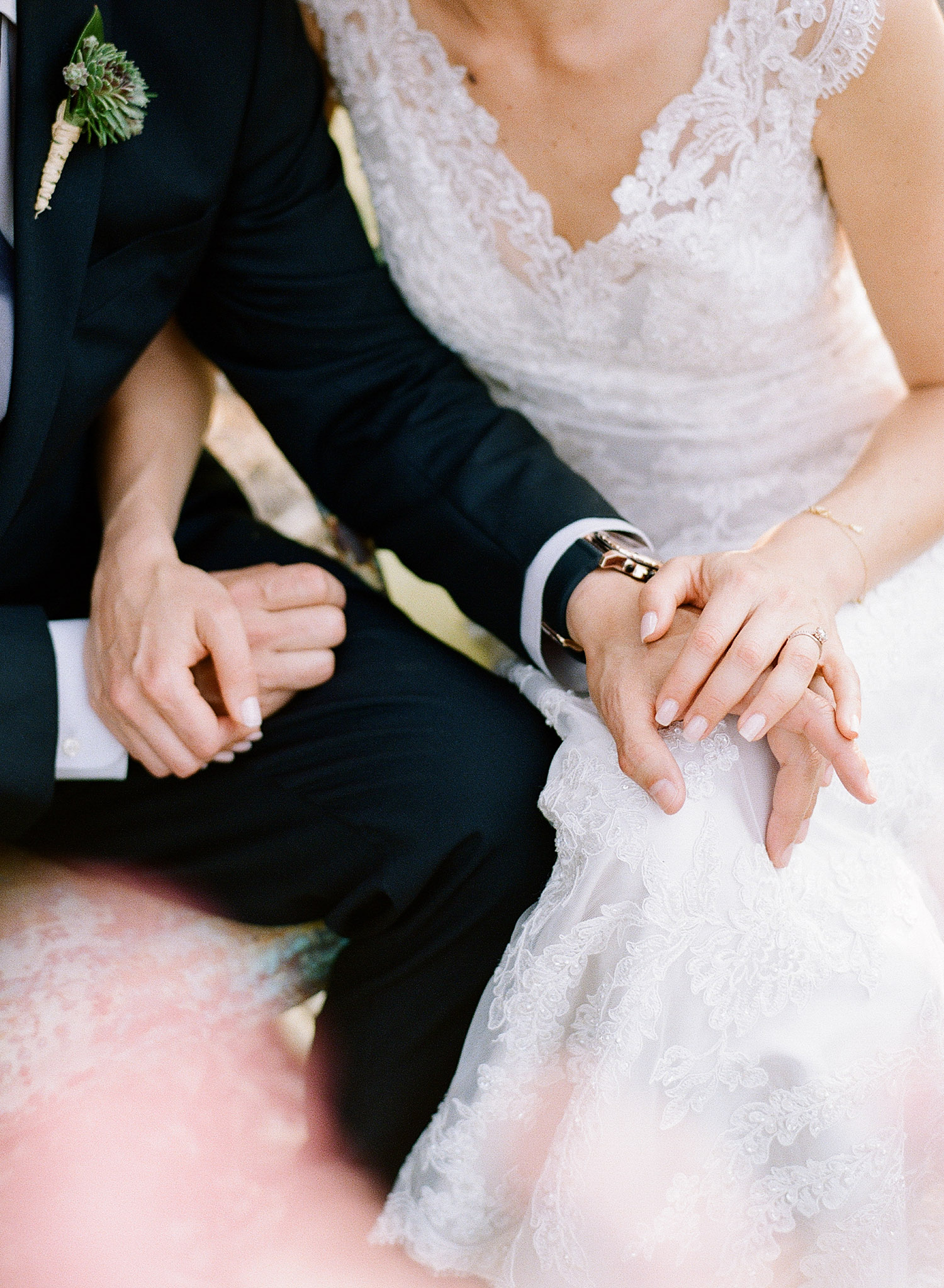 bride and groom hold hands through the pink springtime blooms at this springtime wedding at Northwind Perennial Garden - a beautiful wisconsin wedding venue - while Destination wedding photographer Lexia Frank Photographs this wedding on film