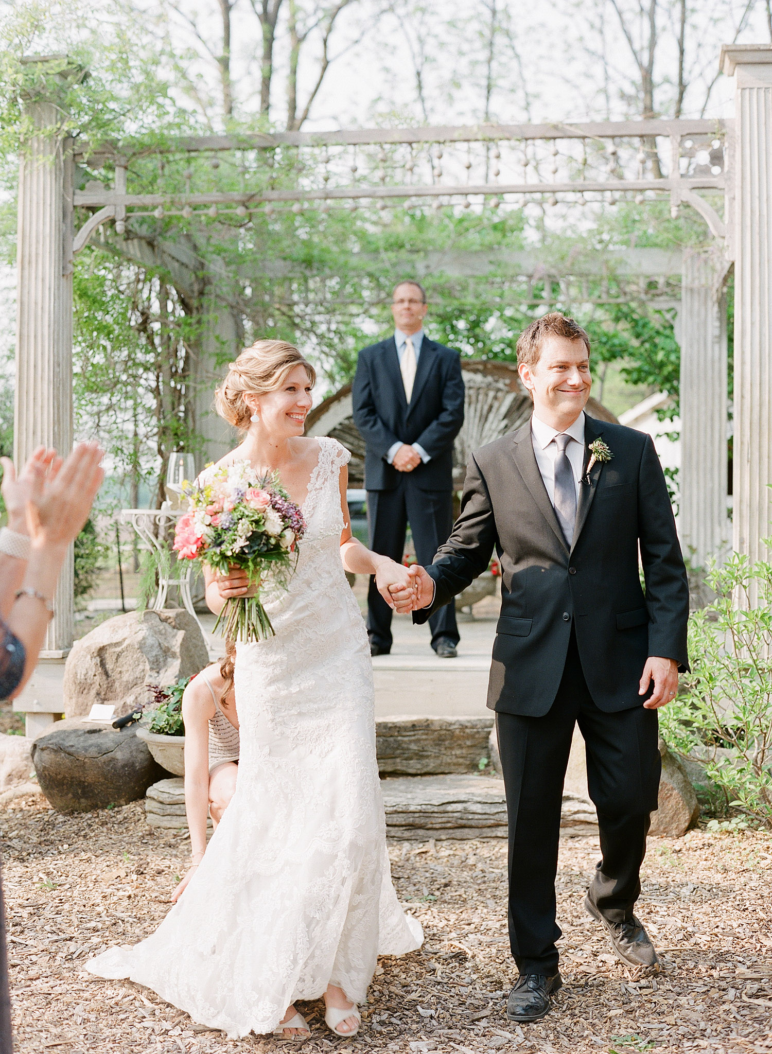 bride and groom walk down the aisle at this springtime wedding at Northwind Perennial Garden - a beautiful wisconsin wedding venue - while Destination wedding photographer Lexia Frank Photographs this wedding on film
