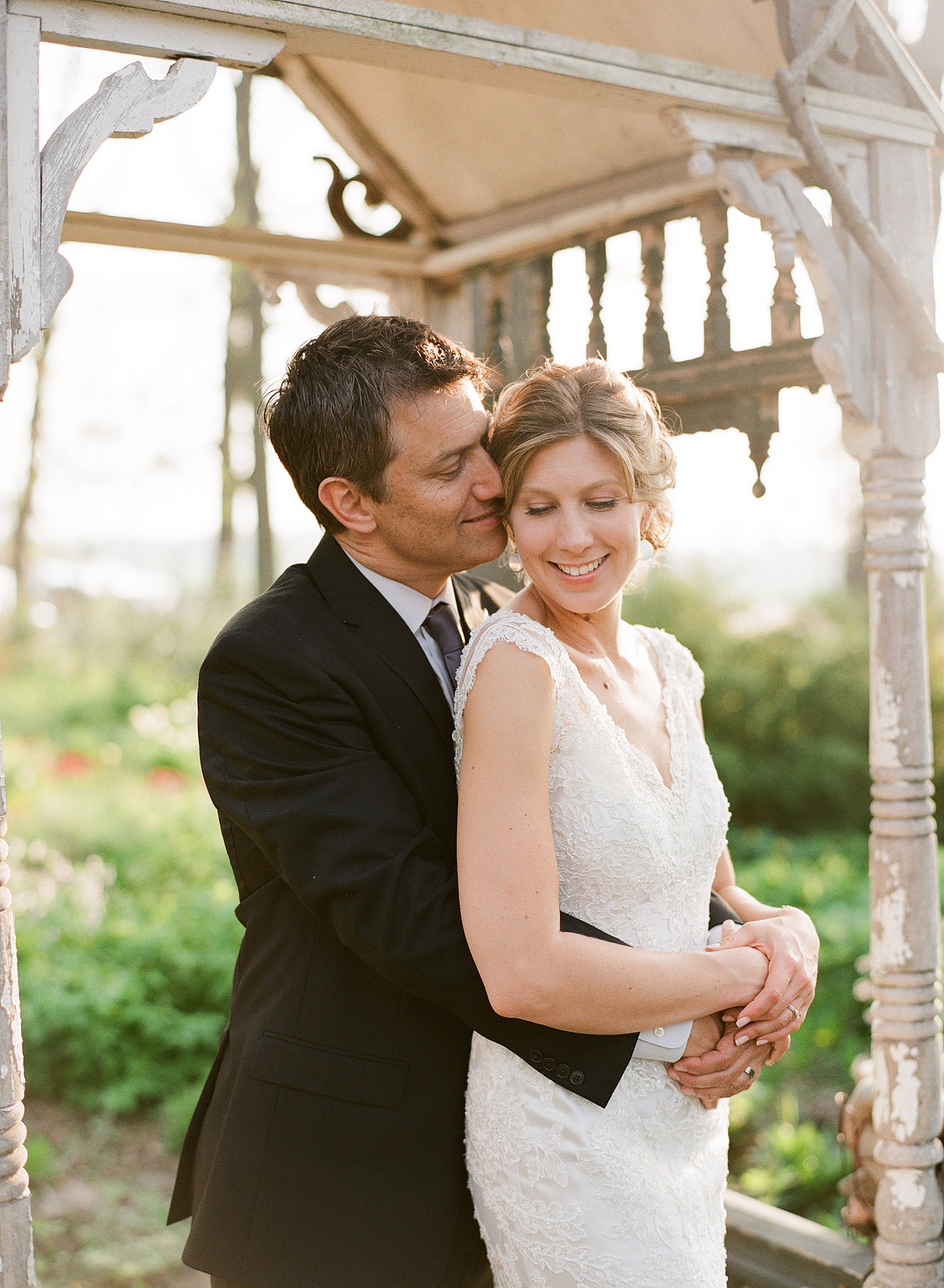 bride and groom kiss in the gazebo at  this springtime wedding at Northwind Perennial gardens - a wisconsin wedding venue - as a film wedding photographer Lexia Frank photographs this destination wedding on film