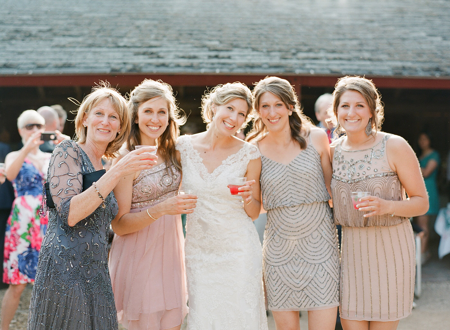 bridesmaids share a cocktail at the outdoor reception at Northwind Perennial Gardens - a gorgeous outdoor wedding venue in wisconsin - while film photographer Lexia Frank Photographs this destination wedding