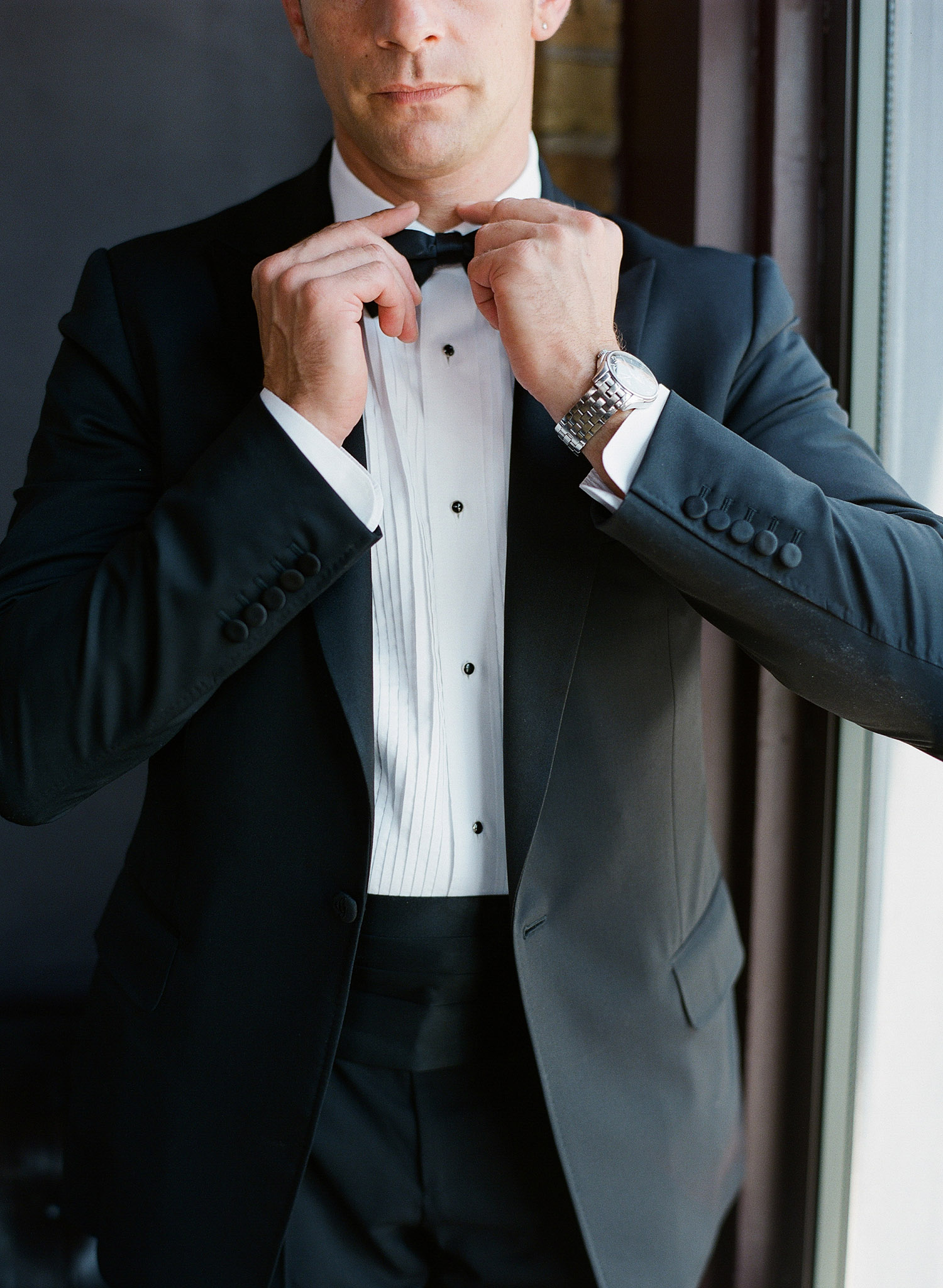 the groom adjusts his bowtie and awaits the ceremony at this beautiful italian villa wedding at the Villa Terrace where International destination wedding photographer, LExia Frank photographs the wedding on film