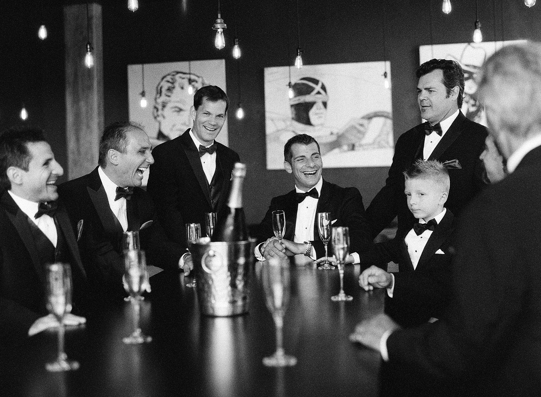 groomsmen share champagne at this italian villa wedding at the Villa Terrace where Destination wedding photographer Lexia Frank photographs this italian wedding on black and white film