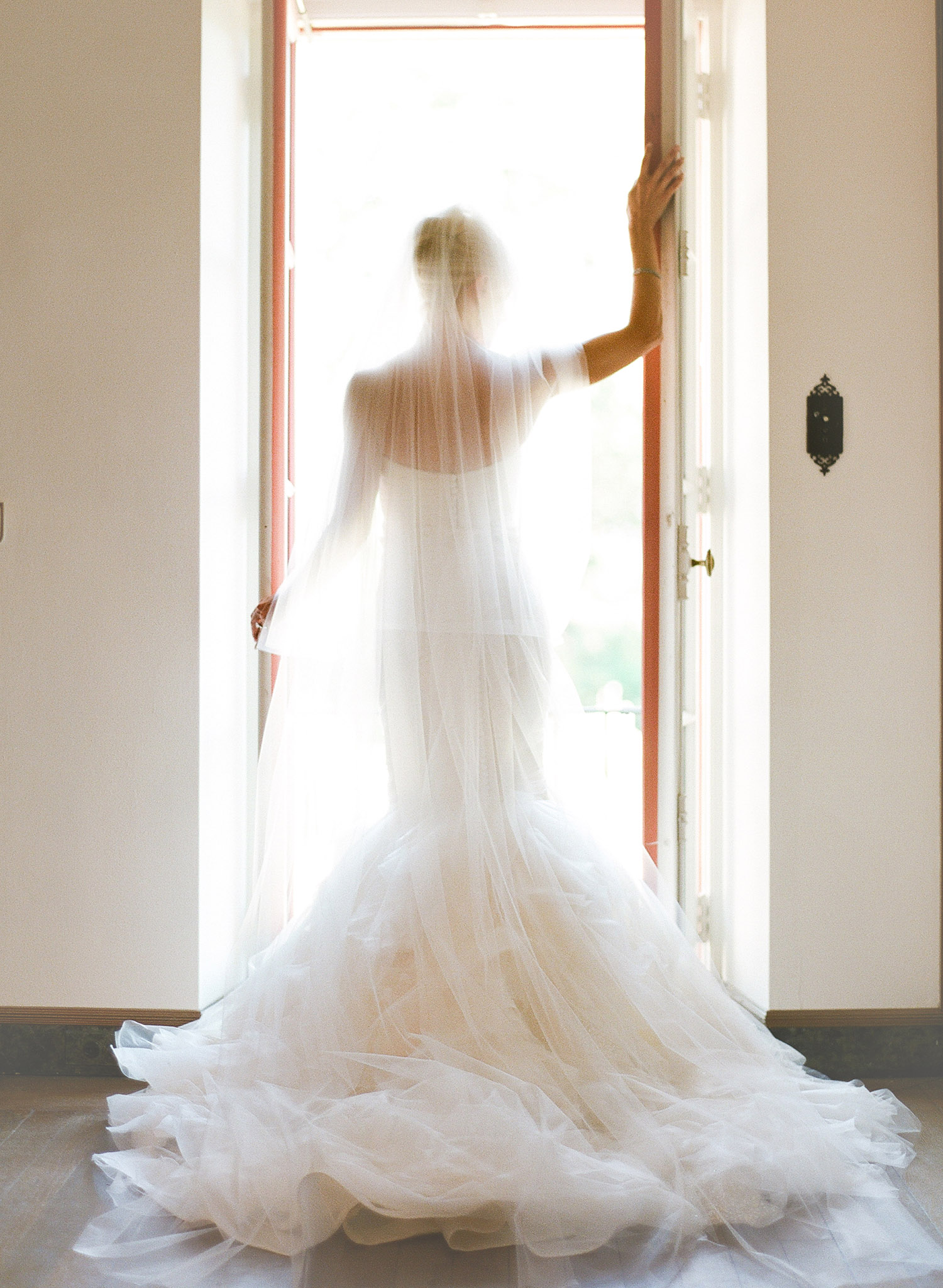 bride stands in a doorway with her huge wedding gown and veil at this Italian Destination Wedding at the Villa Terrace where Destination wedding photographer Lexia Frank photographs the wedding on film as she is a film photographer for weddings