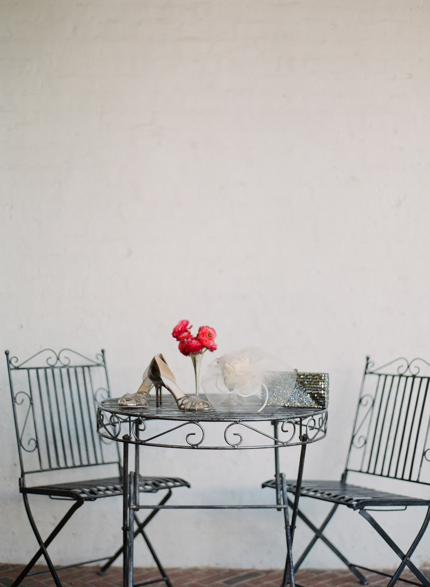 the bride's shoes, veil, and purse sit on a wrought iron table at the Italian Villa The Villa Terrace wedding - a favorite wedding venue of international destination wedding photographer, lexia frank, who is a film photographer for luxury destinations worldwide.