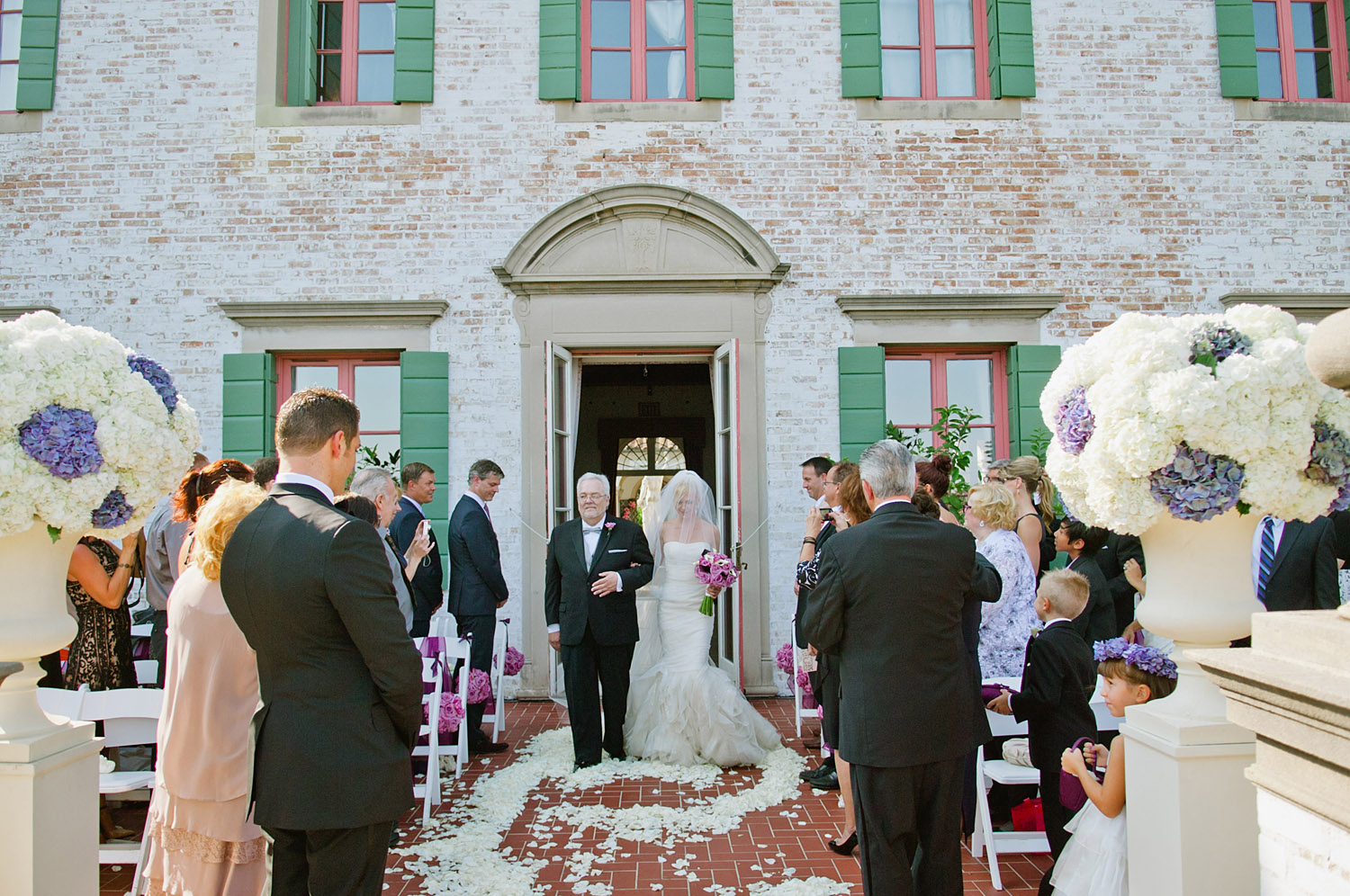 the bride walks down the aisle flanked with purple hydrangeas at this Italian destination wedding at the Villa Terrace - a favorite wedding venue of destination wedding photographer Lexia Frank, who is a film photographer of luxury and estination weddings