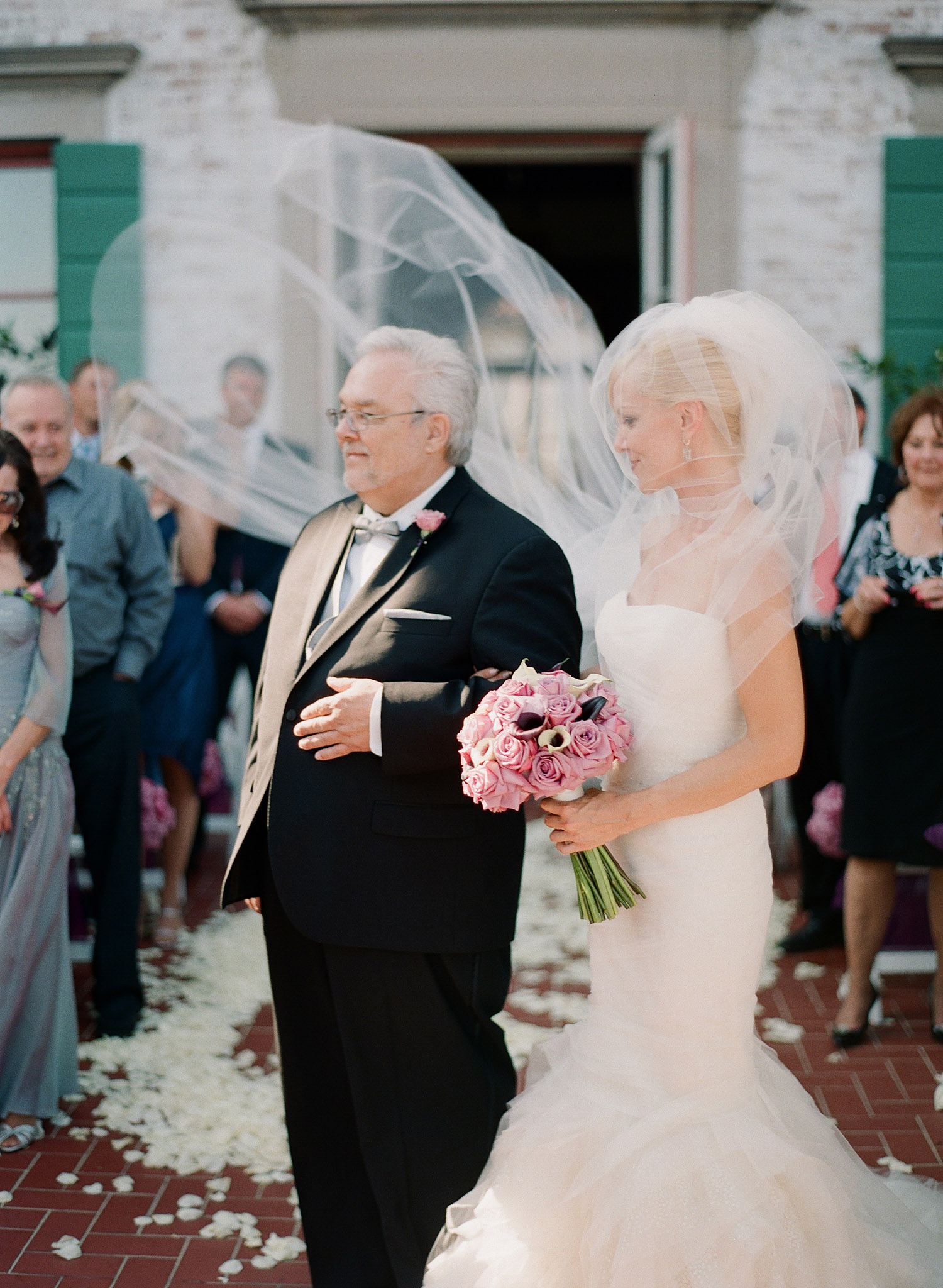 the wind blows the veil of the bride as she stands with her father during her Italian destination wedding at the Villa terrace - a favorite wedding venue of destination wedding photographer Lexia Frank, who is a film photographer of Luxury Weddings