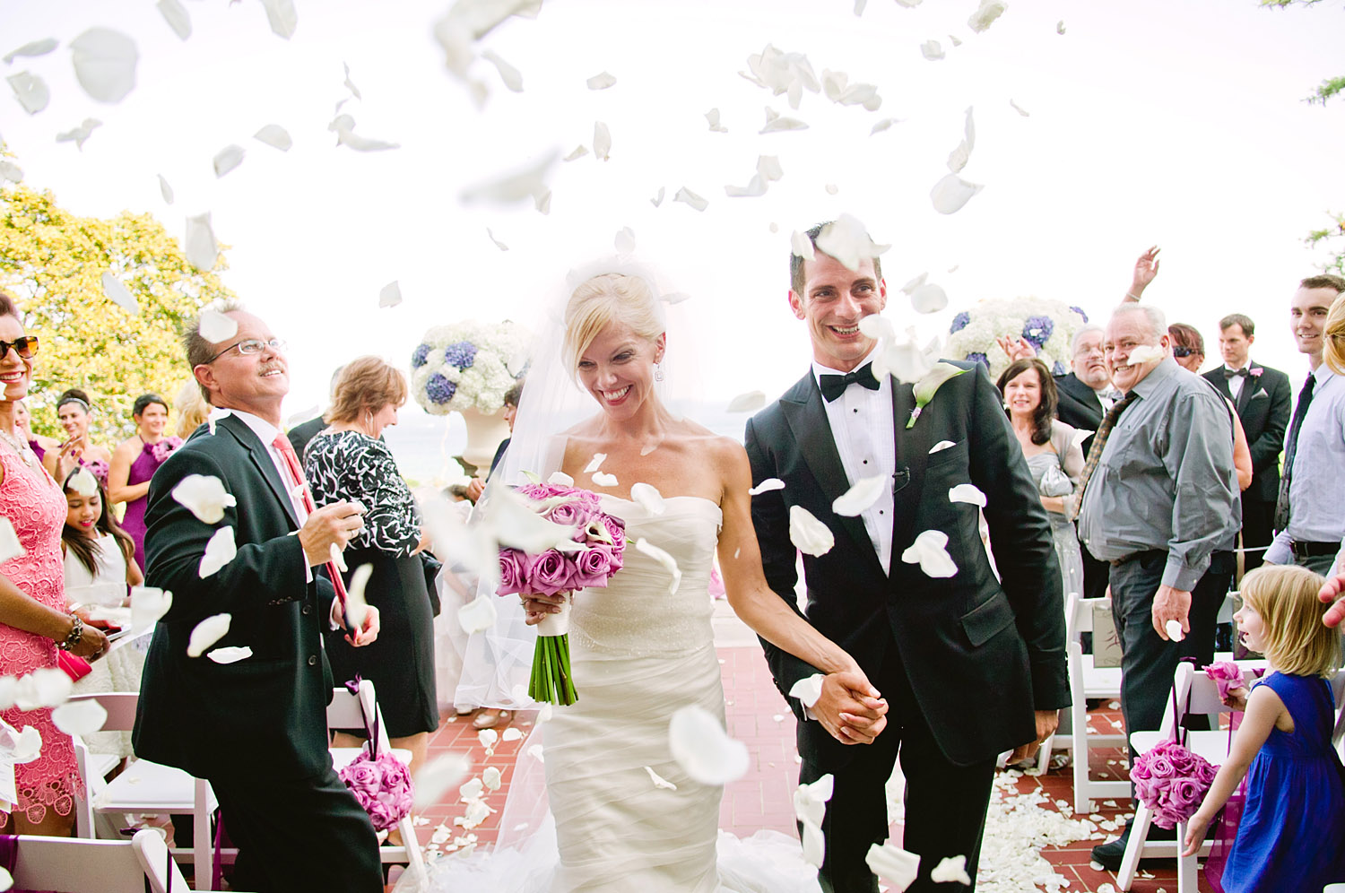 the bride and groom exit the ceremony with guests throwing rose petals at their Italian Destination Wedding at the Villa Terrace - a favorite wedding venue of Destination WEdding Photographer, Lexia Frank, who is a film photographer for luxury weddings