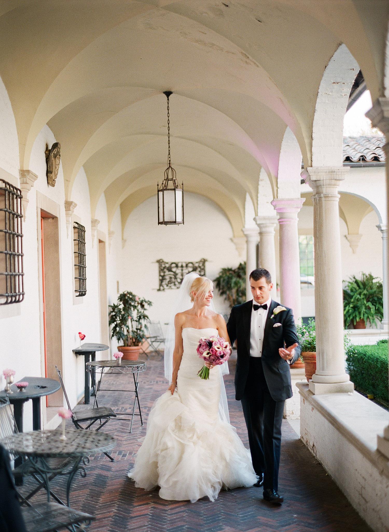 groom leads a bride through the columned corridors of the italian villa at their destination italian wedding while Destination wedding photographer lexia frank photographs their wedding on film at the Villa Terrace