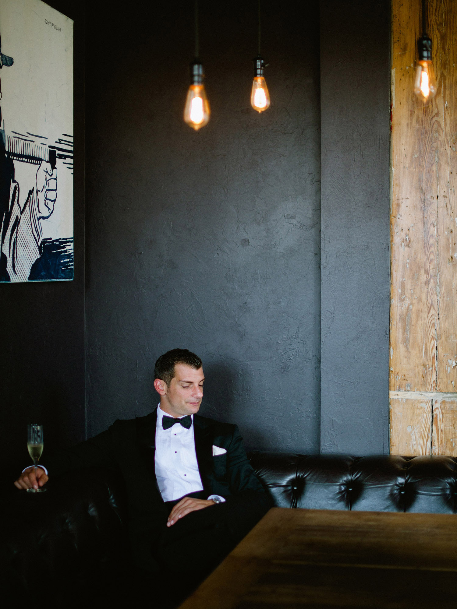 the groom sits and enjoys some champagne at this Italian Villa wedding at the Villa Terrace wedding where international destination wedding photographer Lexia Frank photographs the wedding on film because she is a film photographer for weddings internationally