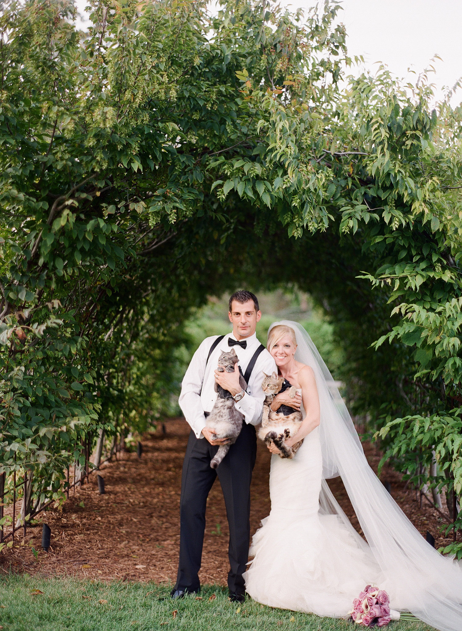 the bride and groom hold their cats dressed in tuxedos for their wedding. great idea for cats in a wedding. Destination wedding photographer Lexia Frank photographs this Italian wedding at the Villa Terrace wedding on film