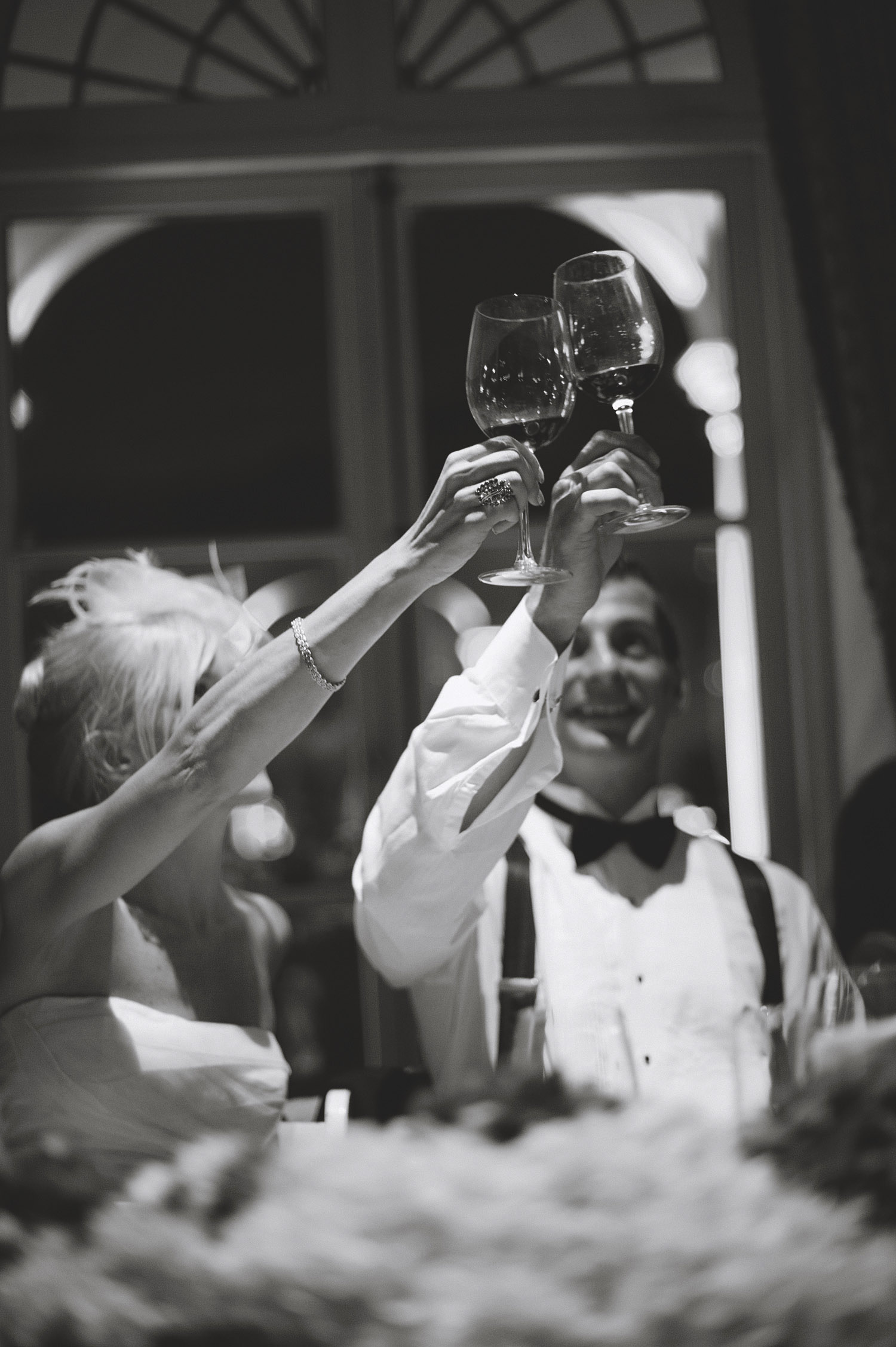 the bride and groom cheers during speeches at the reception of their italian wedding at the italian villa wedding venue, The villa Terrace, while Destination Wedding photographer Lexia Frank photographs the wedding on film