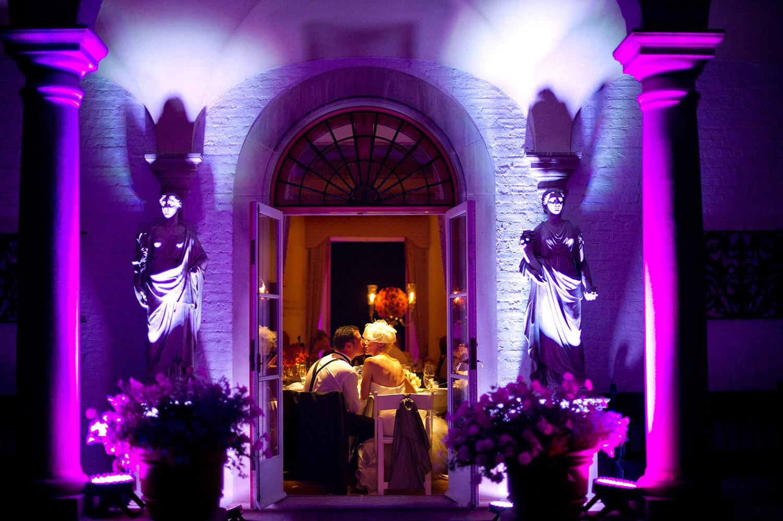 bride and groom share a kiss at the reception of their italian wedding at the Italian Villa, The Villa Terrace, while Destination wedding photographer Lexia Frank photographs their wedding on film