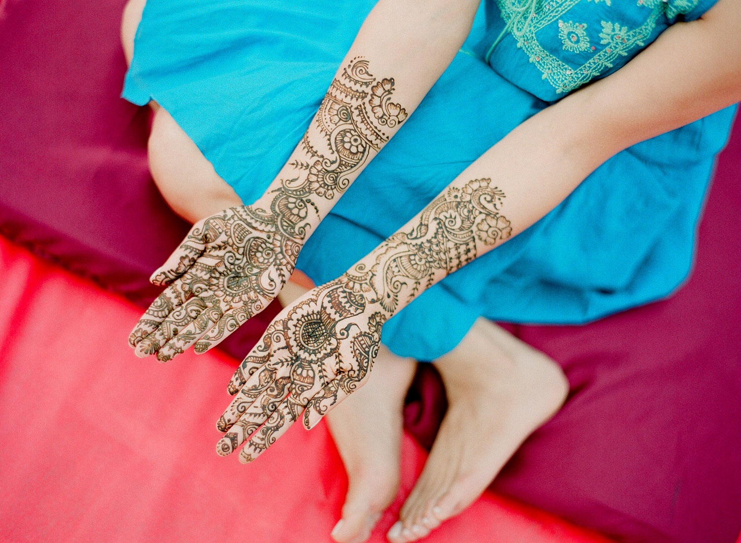 a colorful film photograph of an indian wedding mehndi ceremony in palm coast florida at the hammock beach resortwith a beautiful minimalist mehndi design on an indian bride. Destination wedding photographer, Lexia Frank, is a top Indian wedding photographer photographing luxury indian weddings in florida and worldwide on film