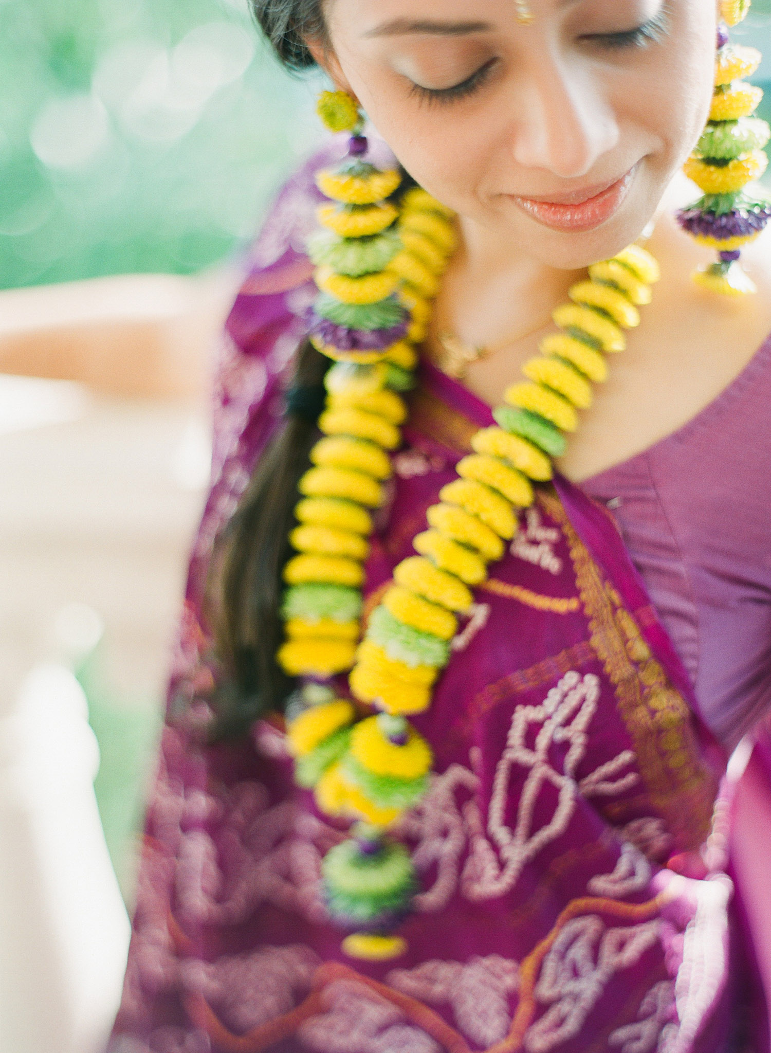 indian bride wears floral jewelry and a floral tikka and floral earrings and a purple sari at this mehndi ceremony in palm coast florida at the hammock beach resort indian wedding. Photographed by destination wedding photographer Lexia Frank, a top indian wedding photographer photographing indian weddings on film and shooting luxury indian weddings worldwide