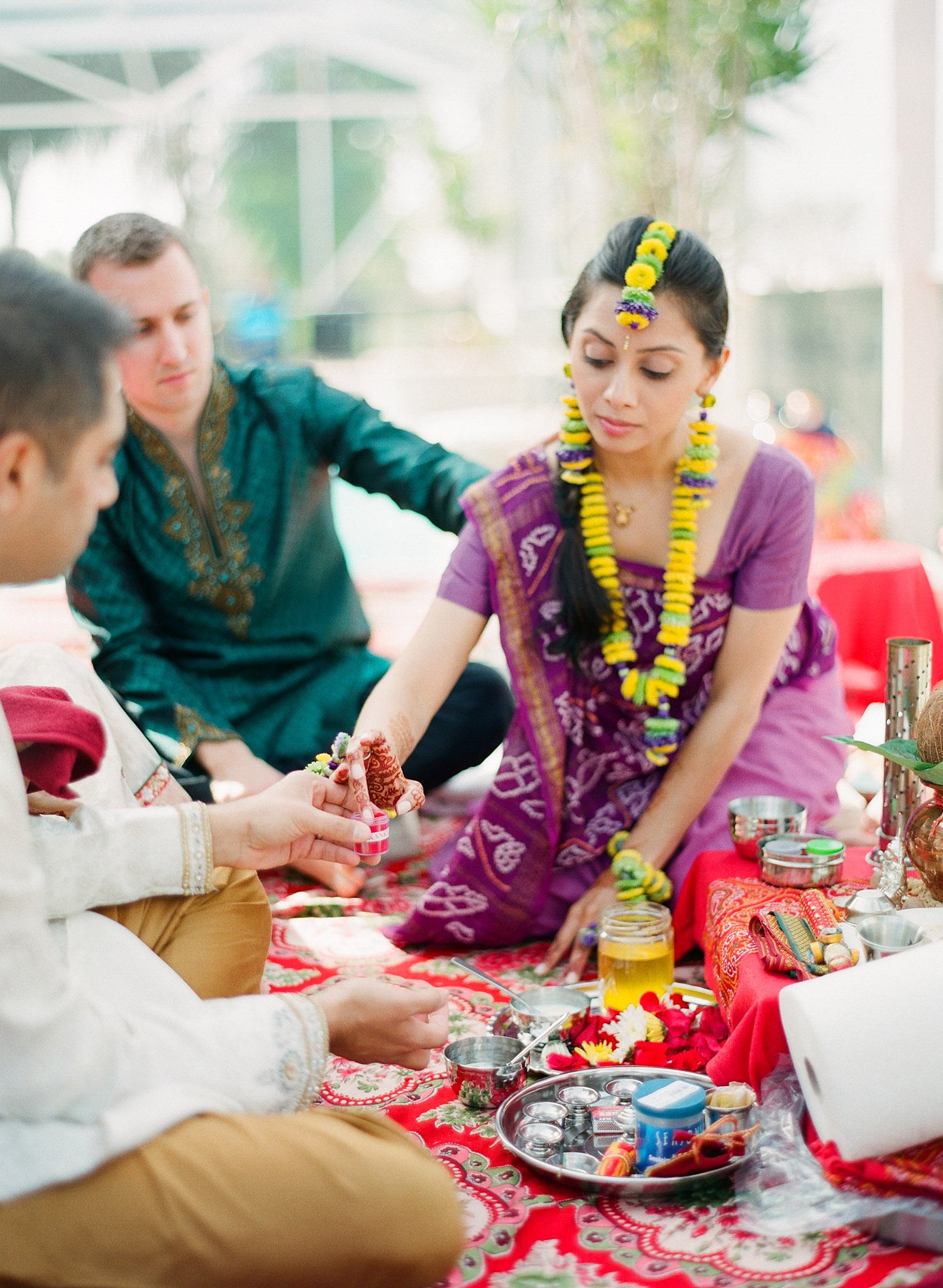 Indian bride at pithi ceremony after her mehndi ceremony in palm coast florida at hammock beach resort photographed by Destination Wedding Photographer, Lexia Frank, a top indian wedding photographer who shoots her indian weddings on film with medium format film cameras and shoots luxury indian weddings in florida and worldwide. bride wears floral jewelry and a floral tikka for her hindu indian wedding