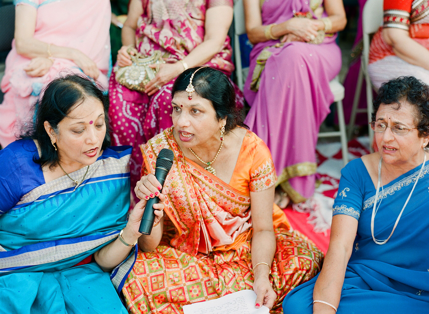 aunties sing at this hindu wedding in palm coast florida at the hammock beach resort photographed by Destination Wedding Photographer Lexia Frank, a top indian wedding photographer photographing her indian weddings on film and medium format film cameras and shooting luxury indian weddings worldwide