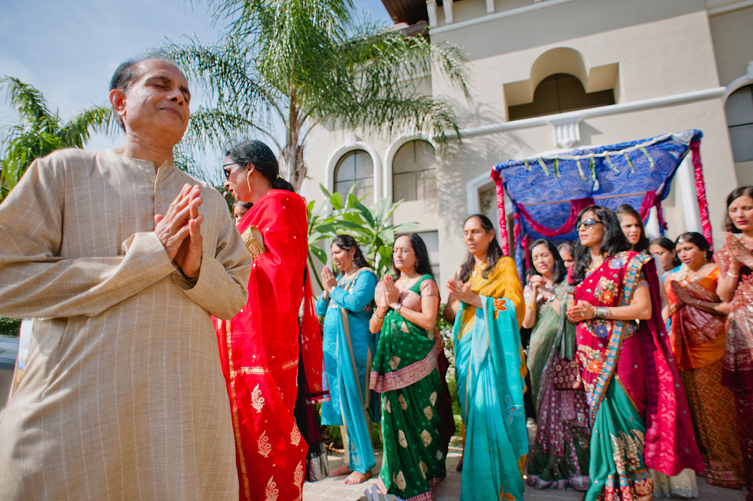 father prays during this pithi ceremony at this hindu wedding in palm coast florida while Destination Wedding Photographer Lexia Frank - a top indian wedding photographer - photographs the day on film because she is a film photographer for indian weddings who still shoots medium format film for weddings