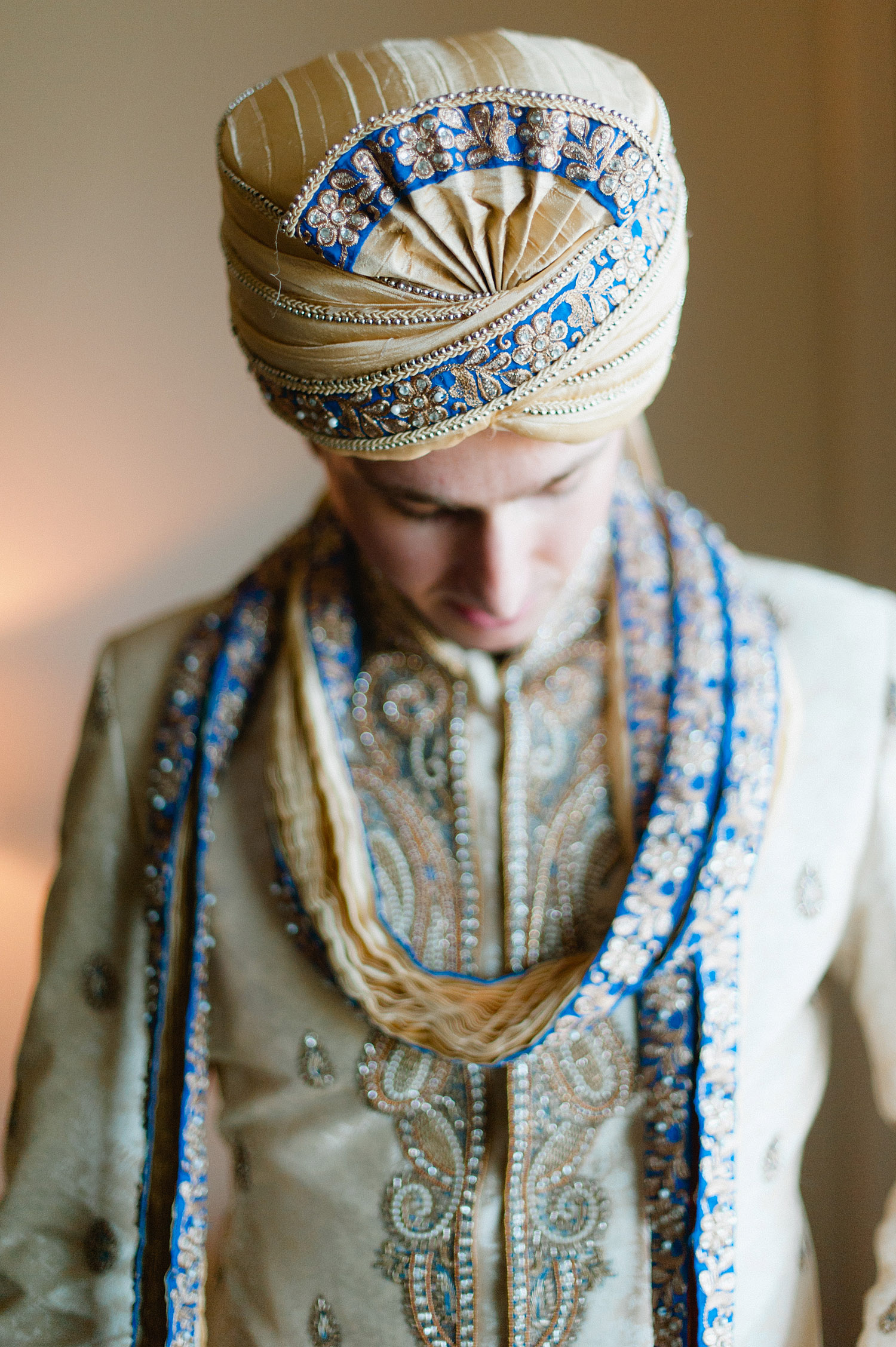 groom gets dressed at his hindu wedding at vizcaya miami where Destination Wedding Photographer Lexia frank - a top indian wedding photographer for luxury indian weddings - photographs this indian wedding on film as she prefers the soft skin tones and vibrant colors for indian weddings in india and worldwide.