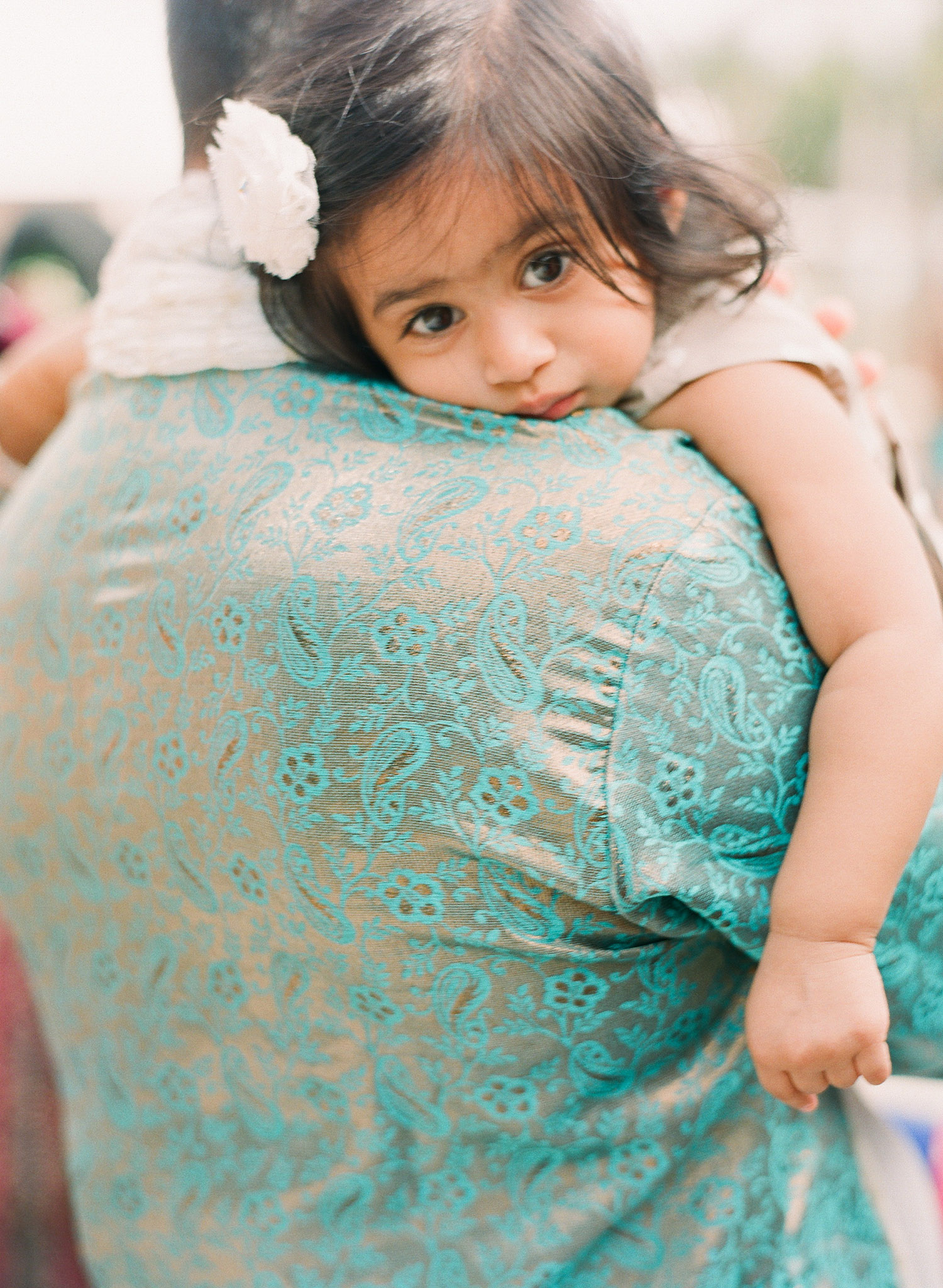 a little girl holds on to her daddy during this parade at the Indian Wedding in Florida photographed by Destination Wedding Photographer, LExia Frank - a top indian wedding photographer - who shoots film for luxury indian weddings preferring the soft skin tones and vibrant colors for indian weddings in india and worldwide