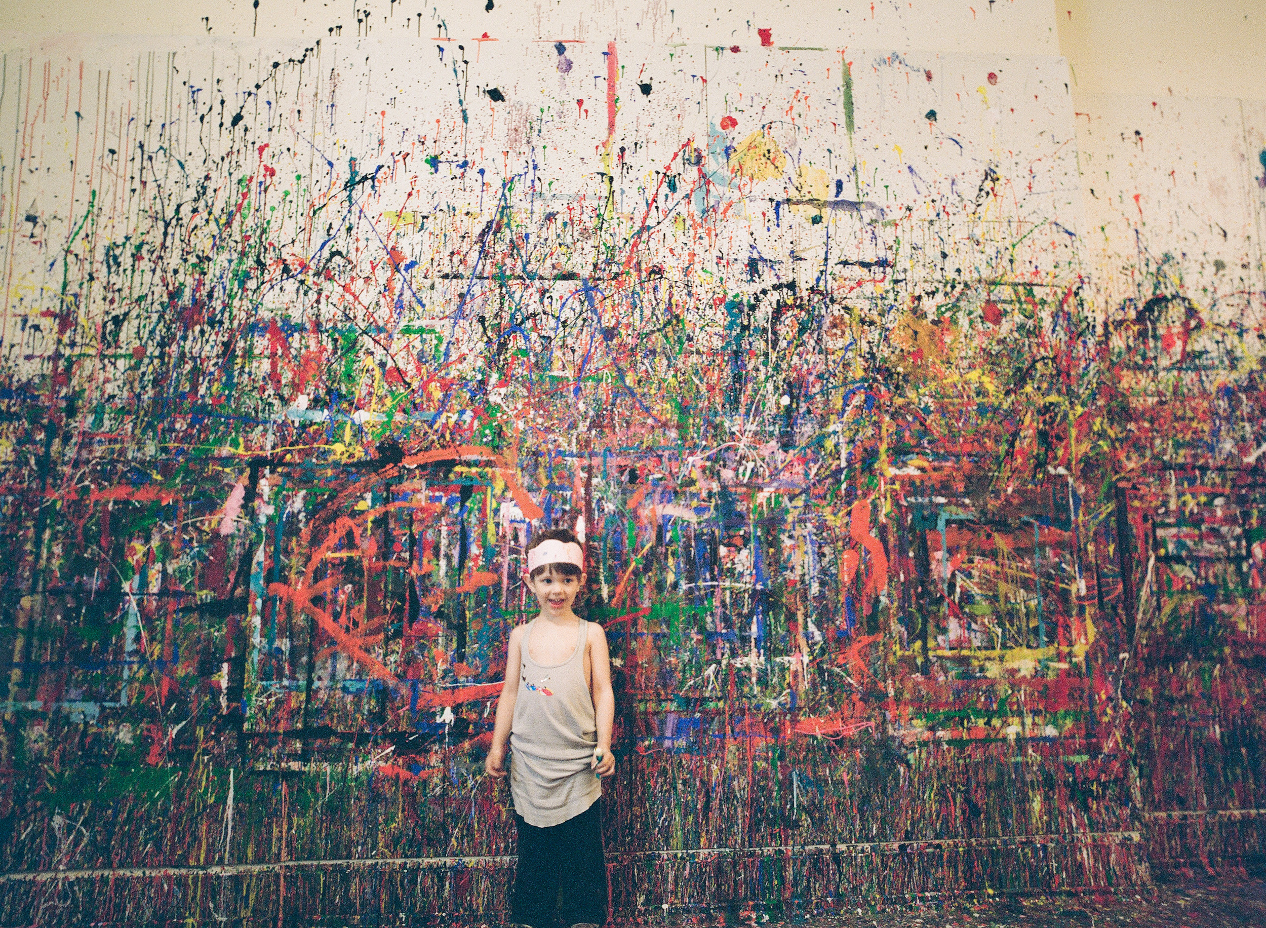 little boy at a painting class against a wall splattered with paint during this lifestyle family session in portland oregon photographed by Portland Oregon Lifestyle Family Photographer - Lexia Frank - a film photographer in portland oregon
