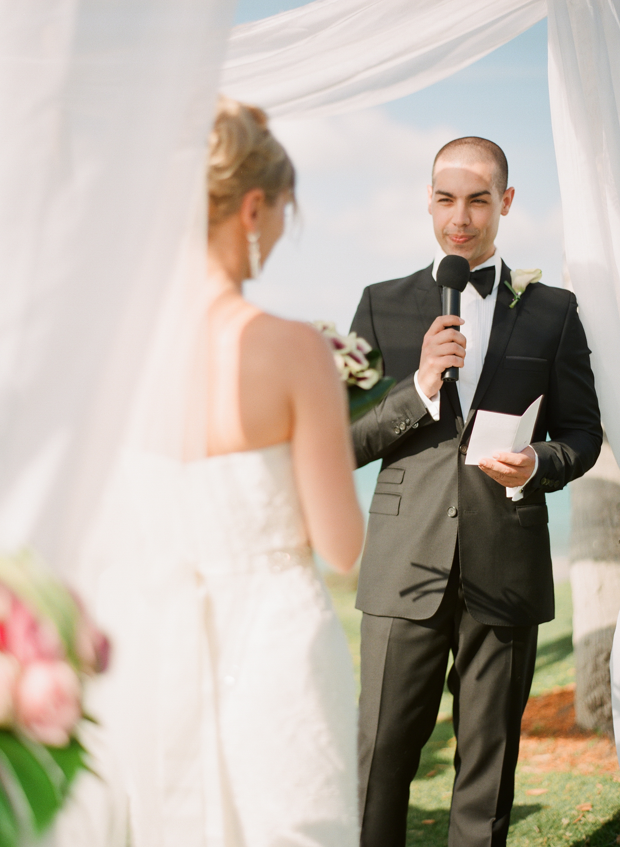 a groom recites his vows under the white canopy during his destination wedding at Vieques Island photographed by Destination Wedding Photographer, Lexia Frank, a film photographer specializing in destination weddings and luxury weddings worldwide.