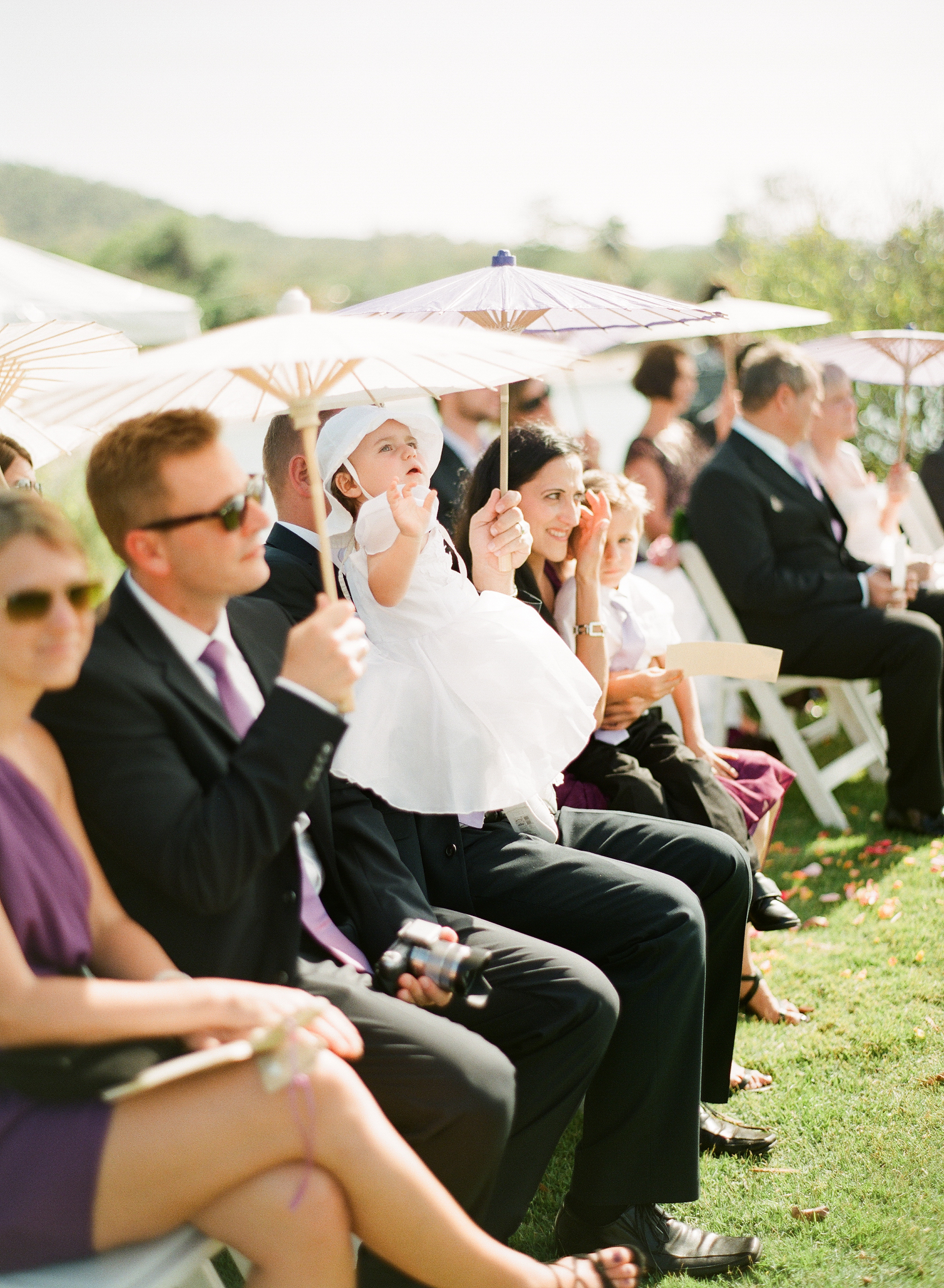 Guests use beautiful shade umbrellas for weddings to shield their faces from the sun during this Destination Wedding at the W hotel on Vieques Island Puerto Rico photographed by Destination wedding photographer, Lexia Frank, a film photographer specializing in destination weddings and luxury weddings worldwide.