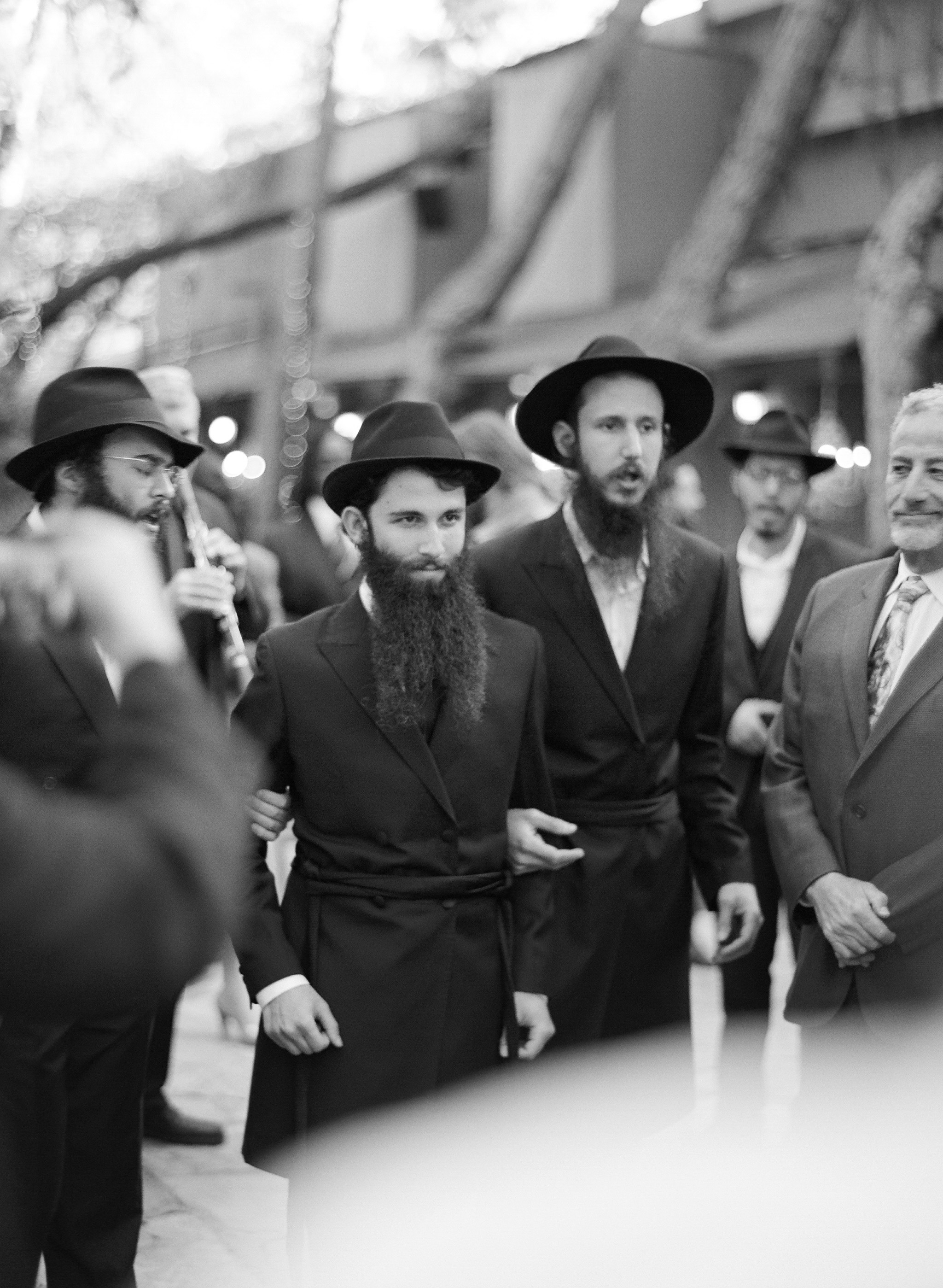 Destination Wedding Photographer Lexia Frank is a film photographer on the west coast specializing in luxury weddings and fine art film photography. In this article she writes a letter to the groom, and talks about the groom's role in photography. in this photo a groom is walked to the bedeken by his groomsmen in this orthodox jewish wedding at Callamigos Ranch Malibu Californiawww.lexiafrank.com