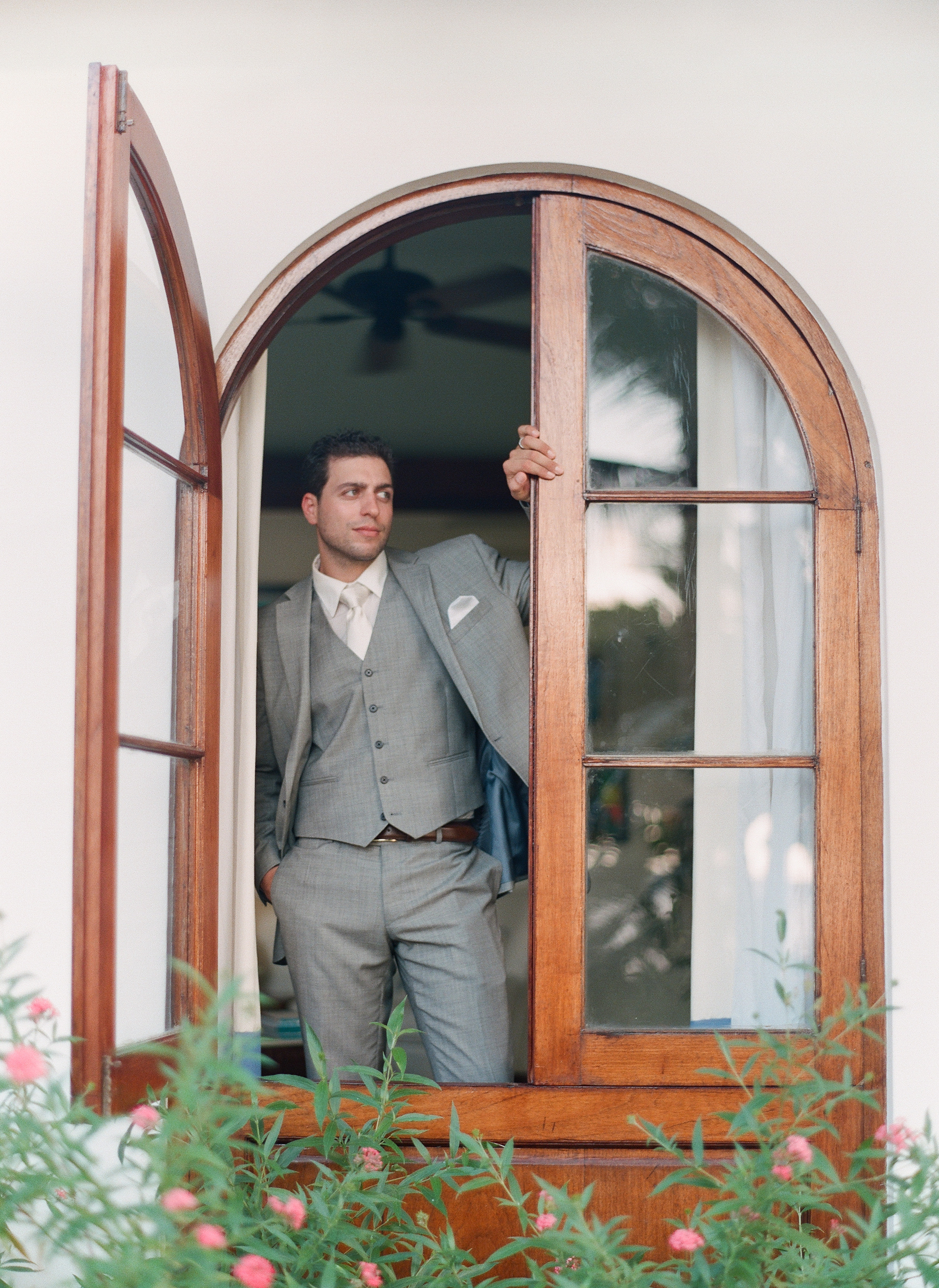 Destination Wedding Photographer Lexia Frank is a film photographer on the west coast specializing in luxury weddings and fine art film photography. In this article she writes a letter to the groom, and talks about the groom's role in photography. Groom poses in a casement window at Roundhill Jamaica before his Roundhill Jamaica weddingwww.lexiafrank.com