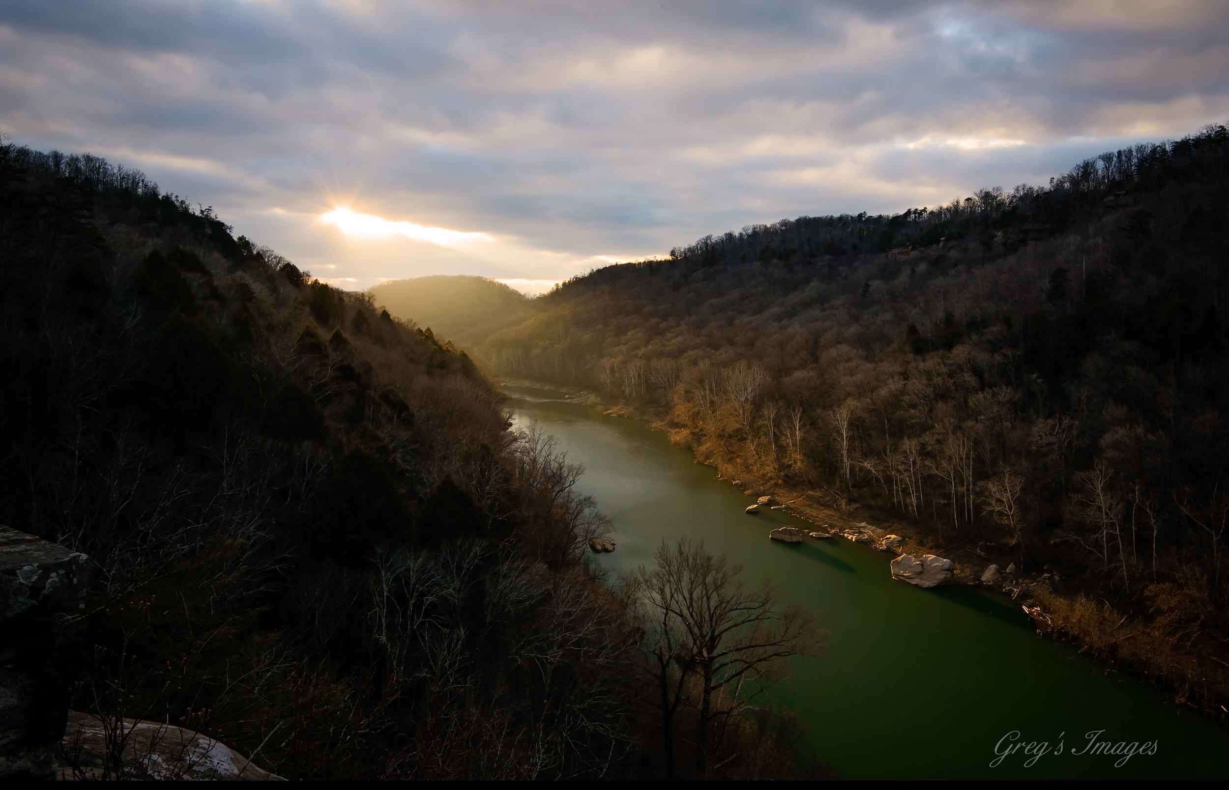 The evening sun breaking through the clouds and illuminating the South Fork River.
