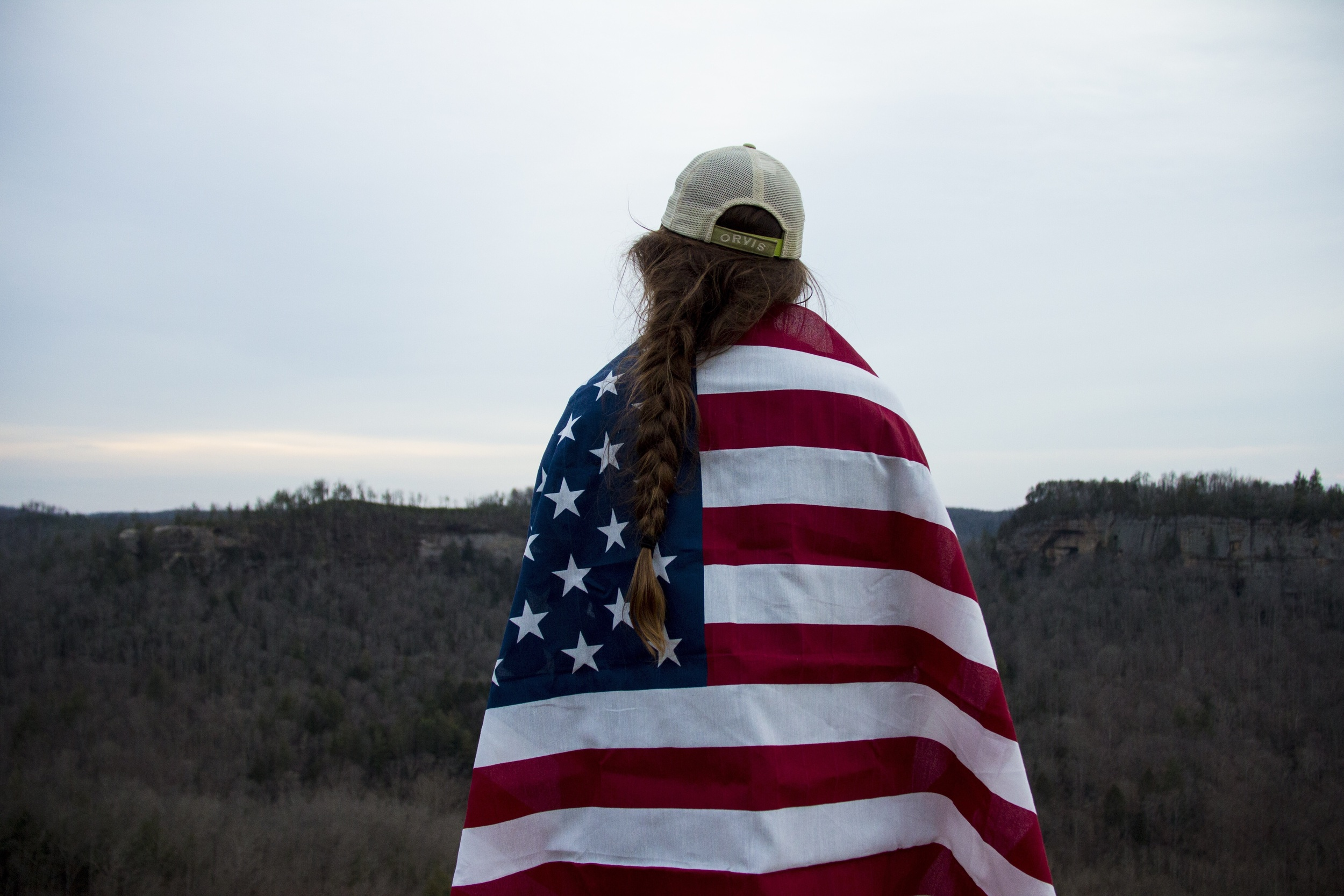 Kelsey holding the American Flag on Chimney Top Rock.