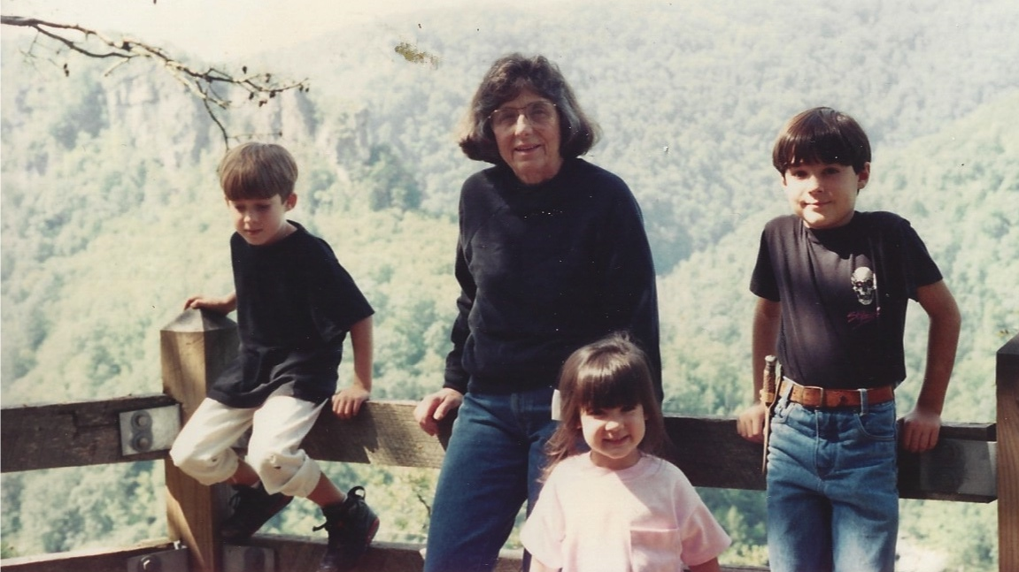 """From the Schmidt Family Archives. Circa 1993. From left to right: the late Covie Schmidt, Kylie's middle brother, maternal grandmother, Grandma Lucy, Kylie, and Cole Schmidt, Kylie's oldest brother.Don't let the pink bow and shirt (didn't get the all black memo) fool you. All she's thinking about is climbing the Towers in the background...and not rubbing Cole the wrong way (""""That's not a knife. This is a knife."""")."""