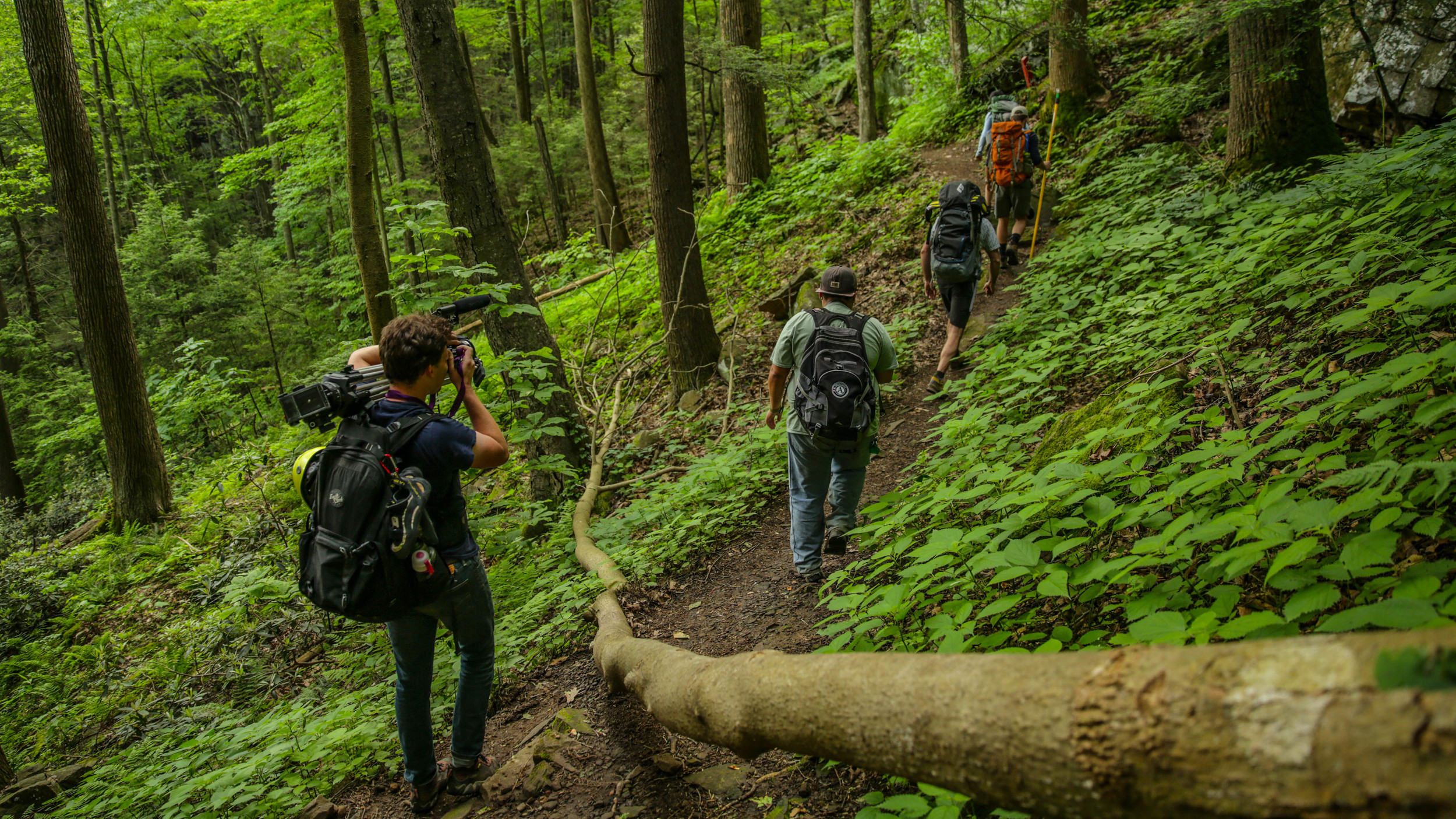 Climber and Filmmaker,Nate Spicer captures the first group of sanctioned climbers at Breaks as they head toward the routes along Prospector Trail.Photo:  Gerry Seavo James