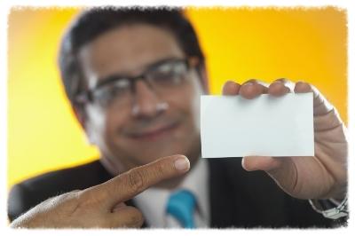 Mature businessman holding blank business card, studio shot