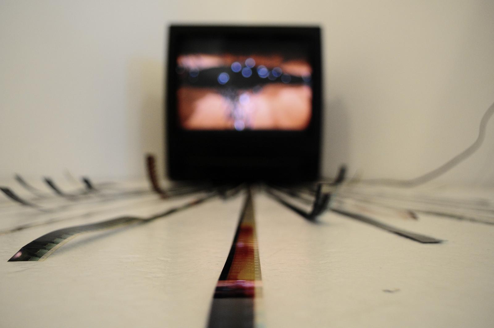 'Möbius' Video installation / TV, 16mm film strips, black acrylic paint.