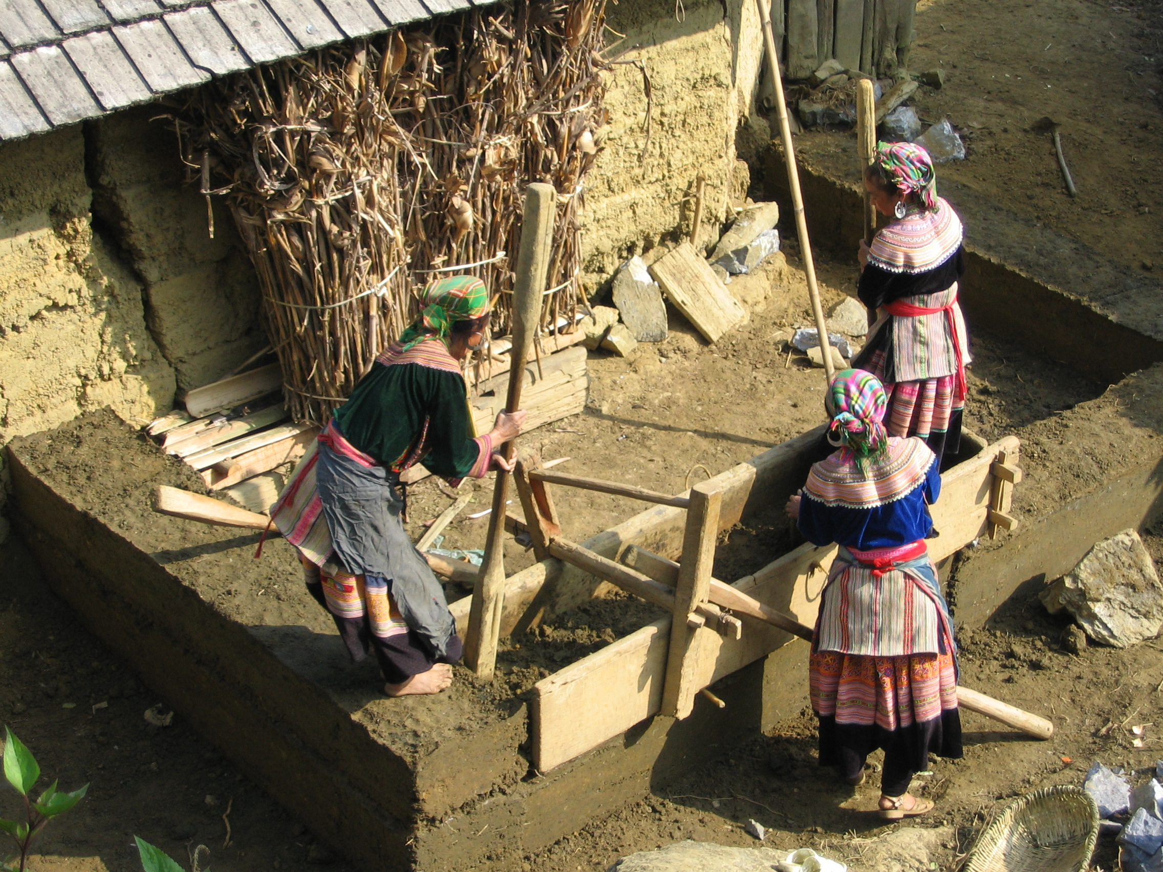 Photo: Flower Hmong woman building a house. Wikimedia Commons. Uploaded by AlfredBoc.