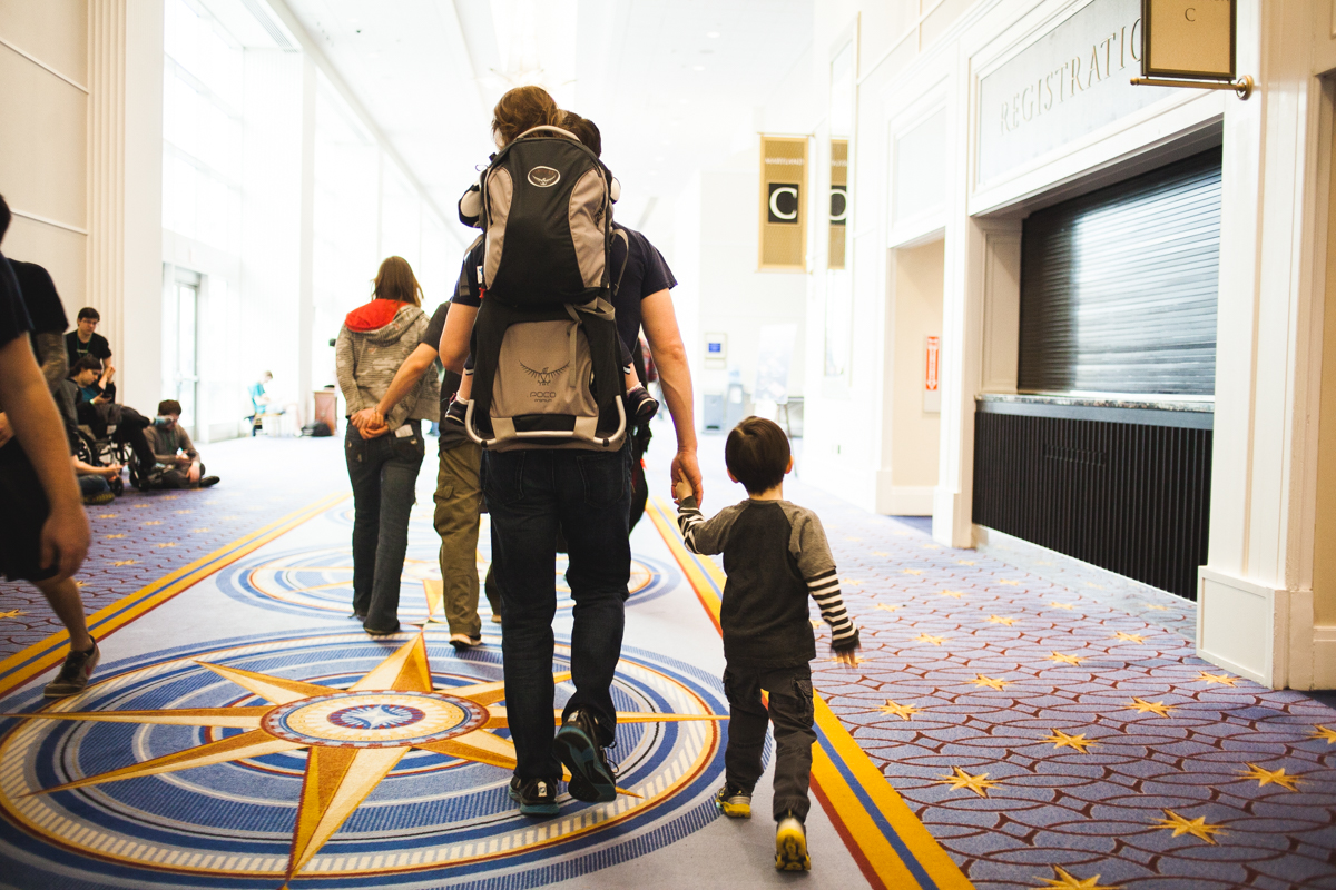 A father leads his children through the different rooms of the convention.