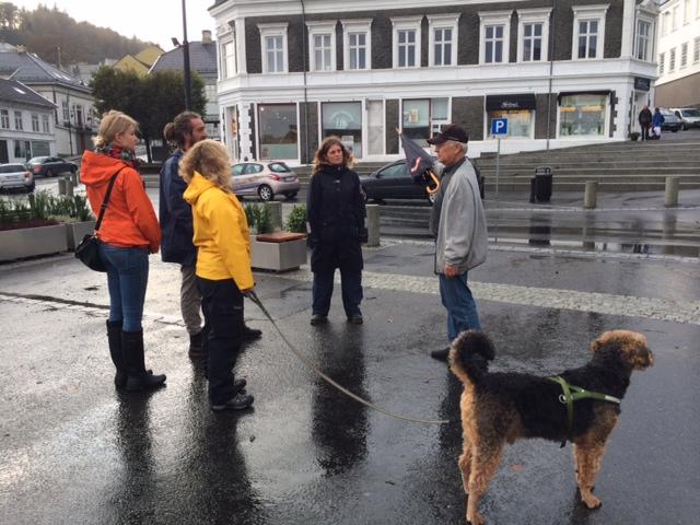 Andrea, Jan Gunnar, Gunhild, Henriette og Ingvild (fotograf) fra Farsund Byforening lyttende til lokalhistoriker Terje Skjoldal. Hunden Hermann var også med på turen.