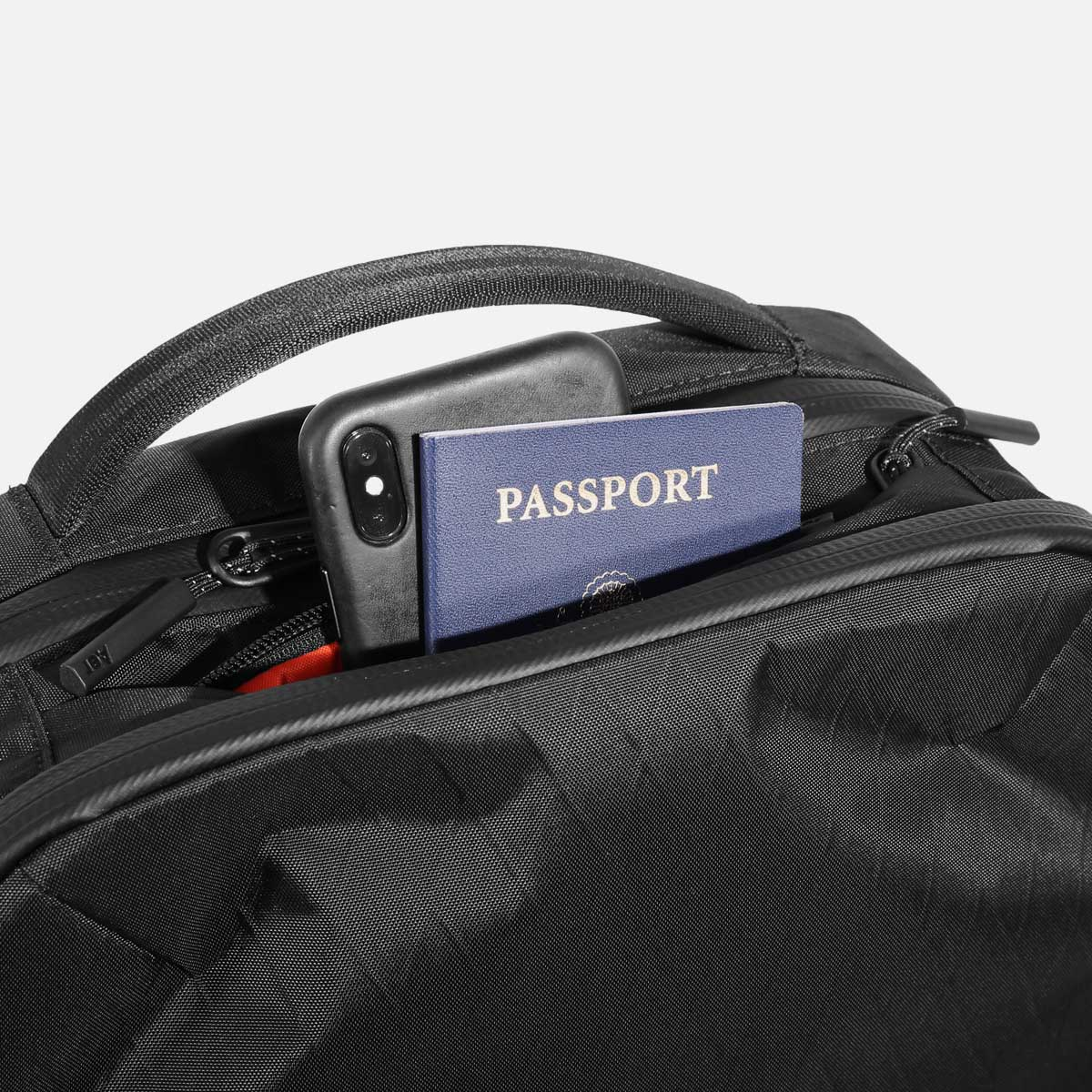 Quick access top pocket for travel documents.