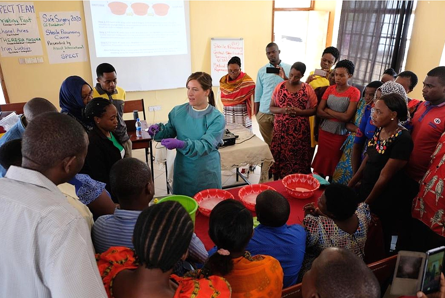 Fast demonstrates the manual instrument cleaning method to Tanzanian training participants.