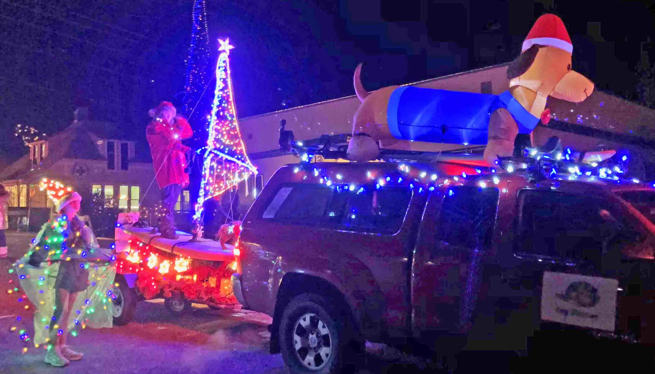 """Surf Dog Diaries in the Hood River Holiday parade. Left to right: Kelsey the Christmas tree girl, Barb and Doodle """"windsurf"""" the streets, Dasher, the 7-foot weiner dog on the roof of Red, the truck. Photo (c): Robb Severdia, DogDiary.org"""