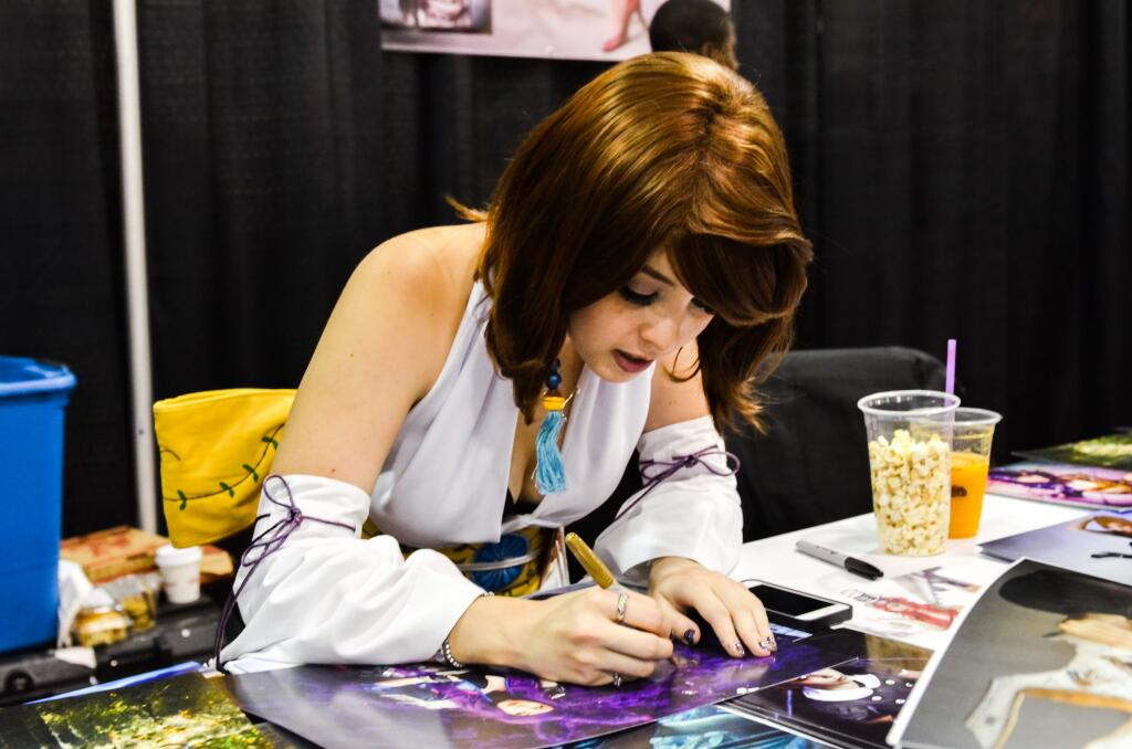 Signing photos for fans at Calgary Expo in 2014.