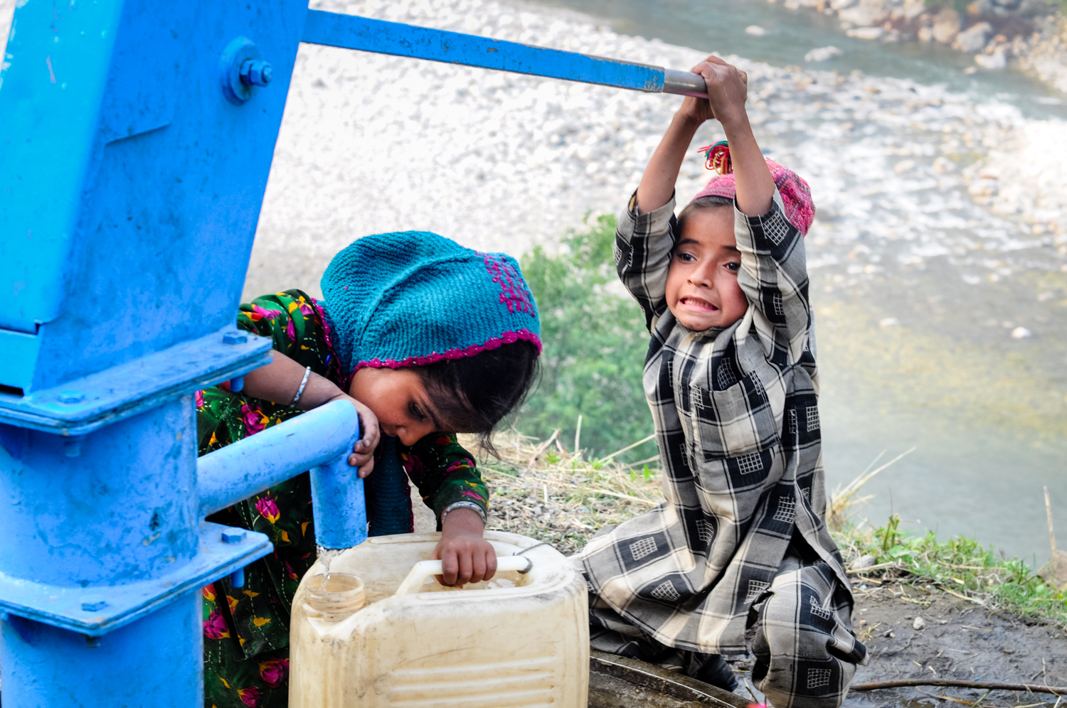 Children are expected to help with chores, to the extent of their ability. Here, Rustem and his sister Djennam Khatoon, fetch water from a roadside pump during the migration.
