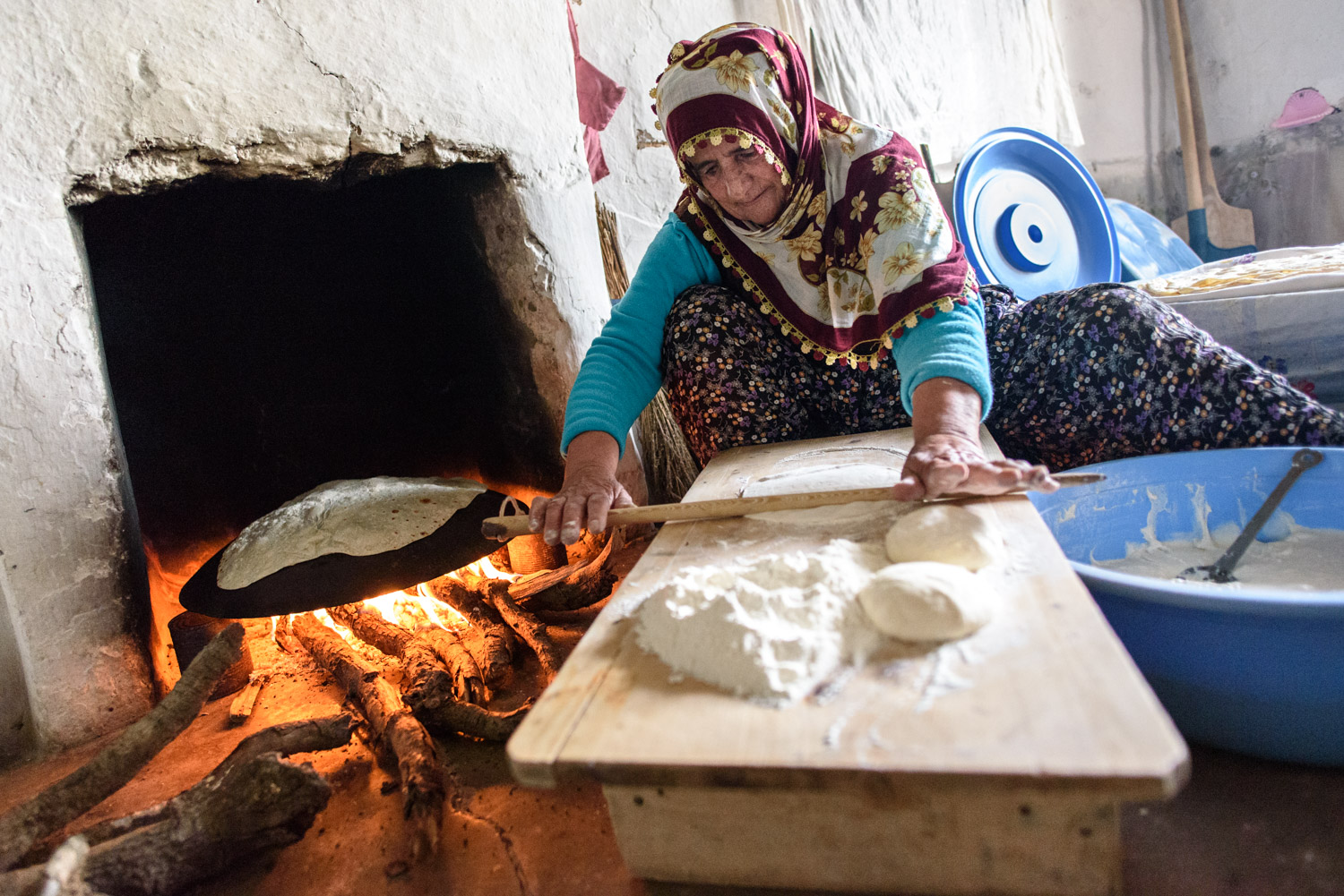 Baking traditional bread over a fire in a home in the Munzur Valley. This batch of bread will be sent to family members living in Istanbul.