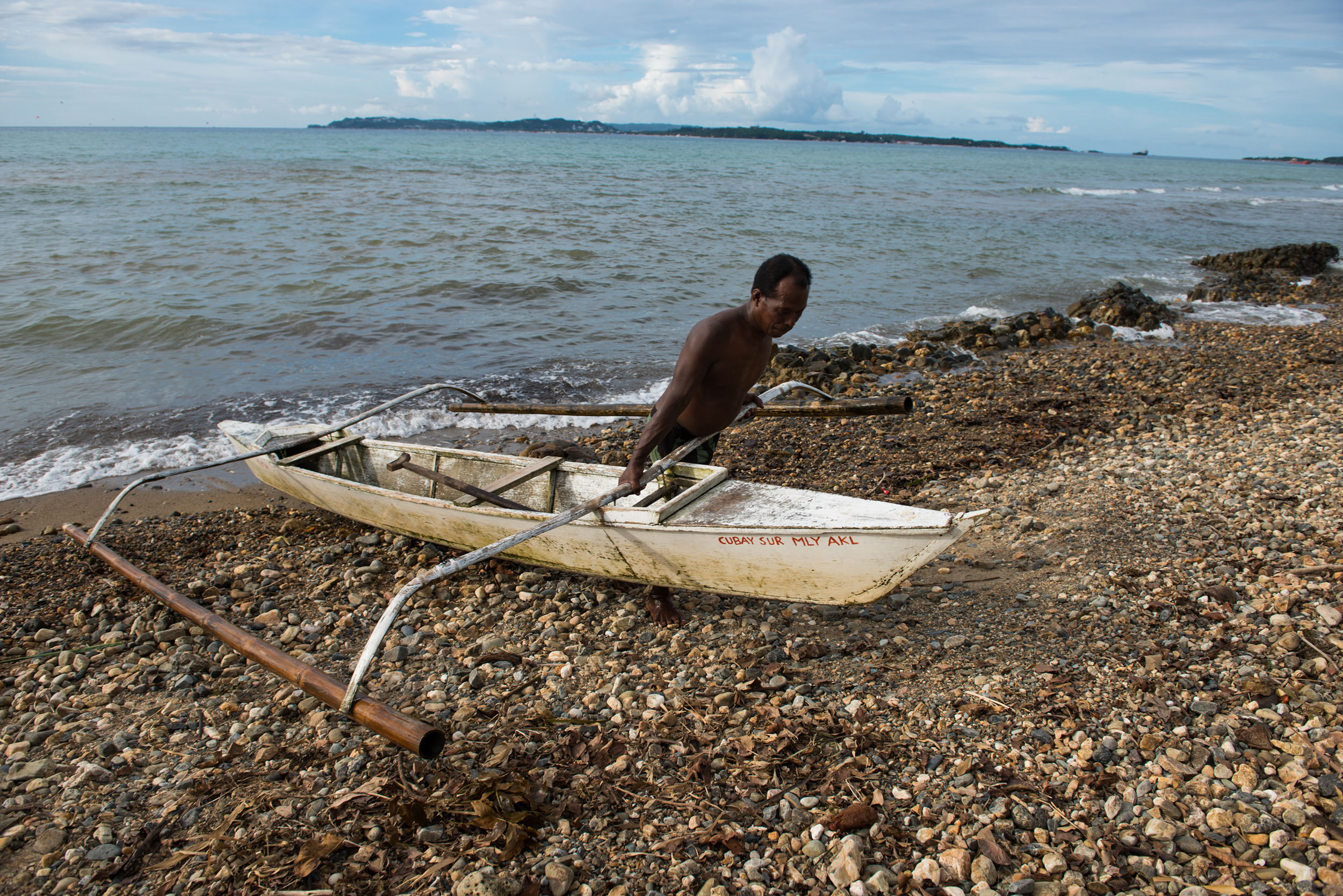 """An Ati man bringing his fishing boat out of the water. Historically, the Atis were nomadic and would rely on gathering wild foods, especially fruits, tubers, roots and honey. While fish have  always been part of their diet, it's become more important than ever, as their other wild food sources have been critically depleted due to deforestation and increased population pressures from the so-called """"lowland"""" - or non-indigenous - peoples."""