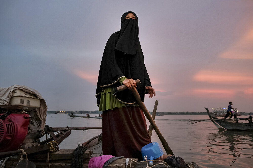 Modern Cham women who live in a fishing community have prospered from working abroad, where they also learned to become more devout. This woman who lived and worked at a supermarket in Malaysia rejoined her devout community in a settlement on the shores of the Mekong River.
