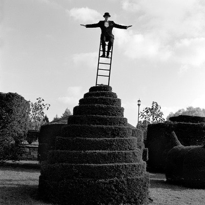 "Travis on Ladder Above Hedges, Longwood gardens, Pennsylvania  2002 Silver gelatin print 10.5 x 10.5"" (image) 22 x 26"" (mount)"